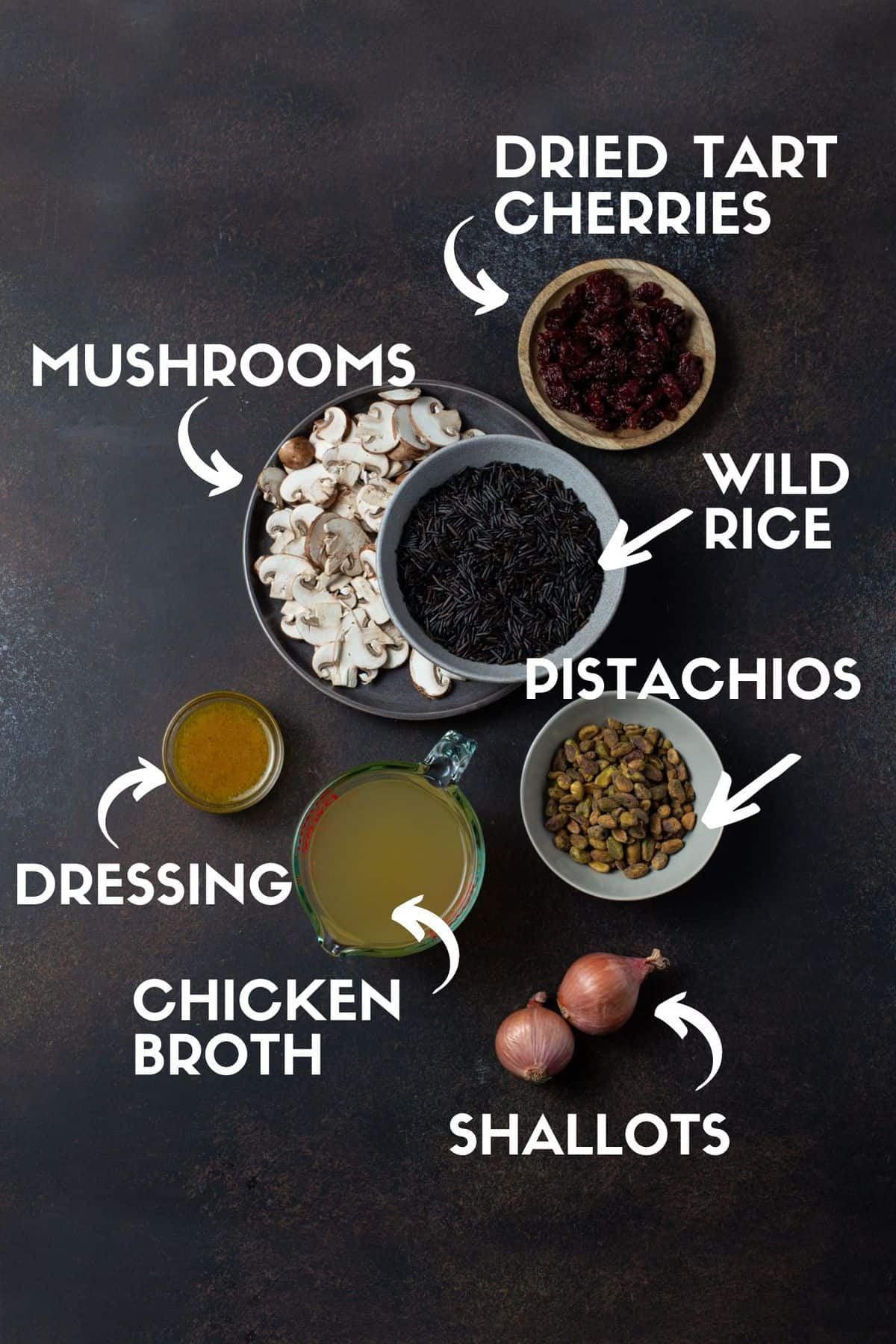 Ingredients for wild rice recipe including wild rice, mushrooms, pistachios, dried cherries, chicken broth, shallots and a maple dijon dressing.