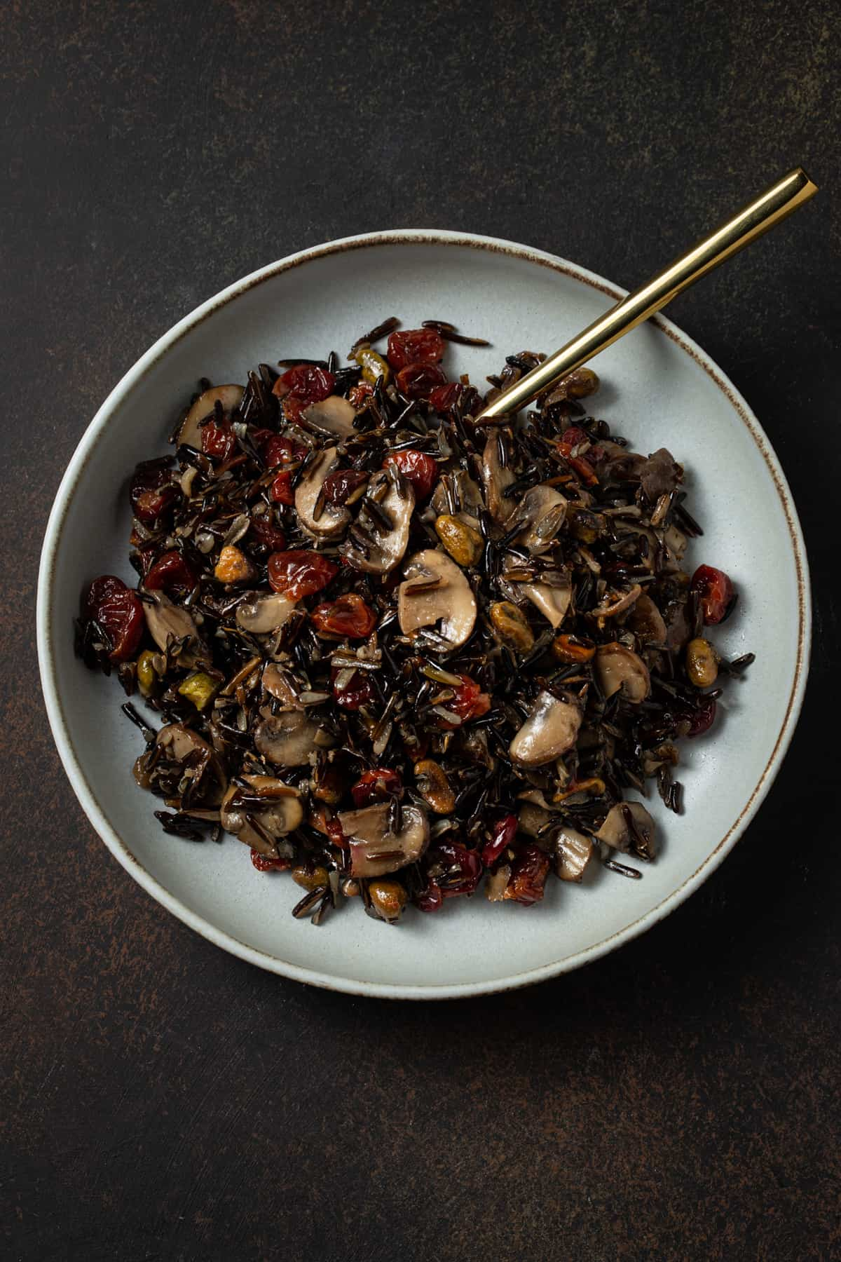 Gray bowl filled with cooked wild rice, mushrooms, cherries & pistachios.