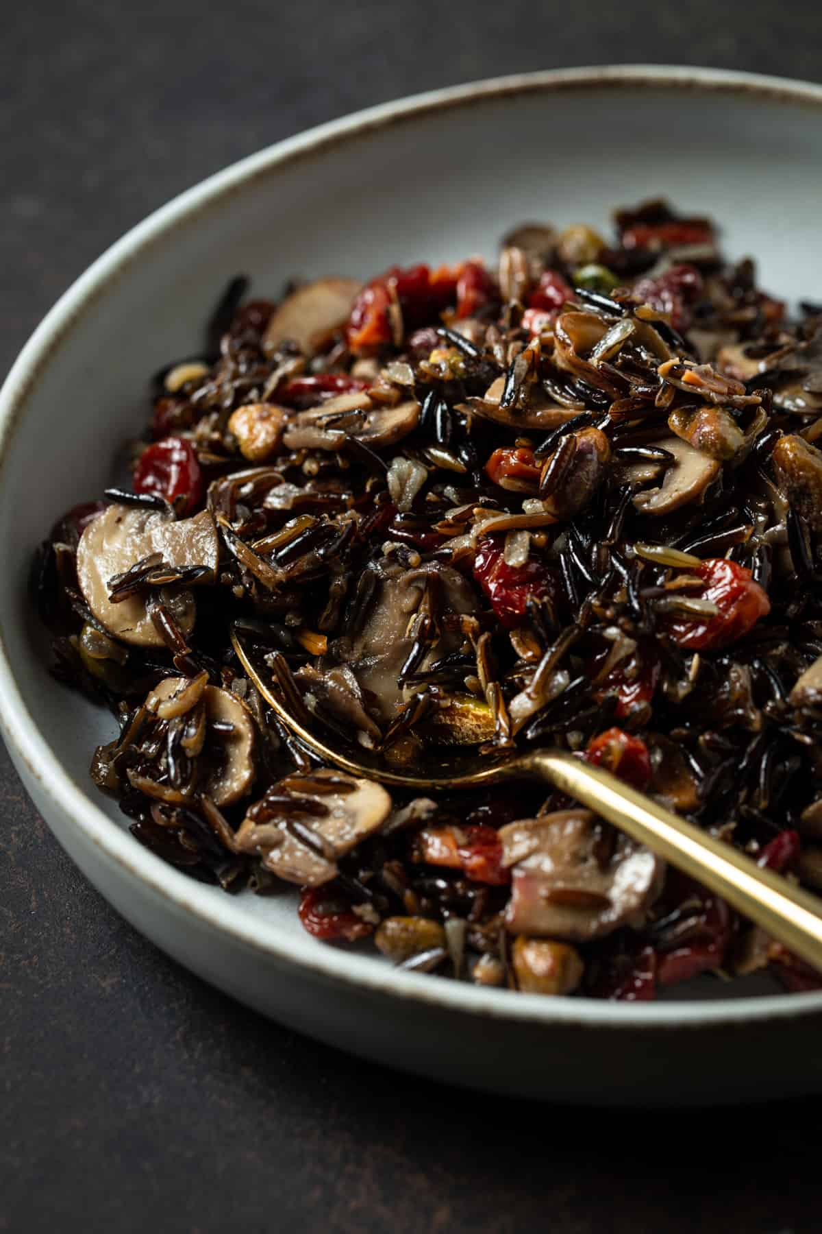 gray bowl filled with cooked wild rice, cherries, mushrooms & pistachios.