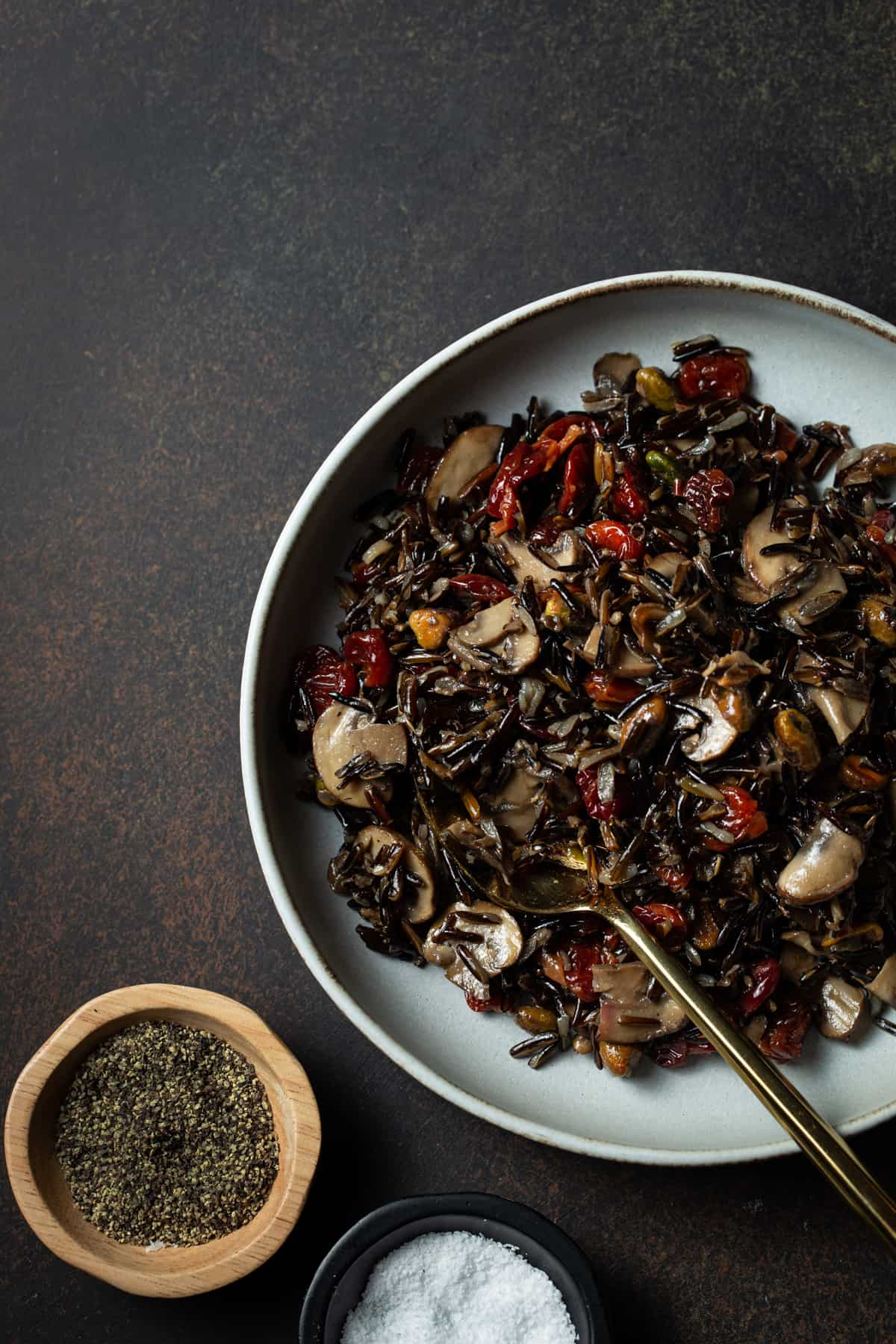 Gray bowl filled with cooked wild rice, pistachios, mushrooms & cherries next to two small bowls of salt & pepper.