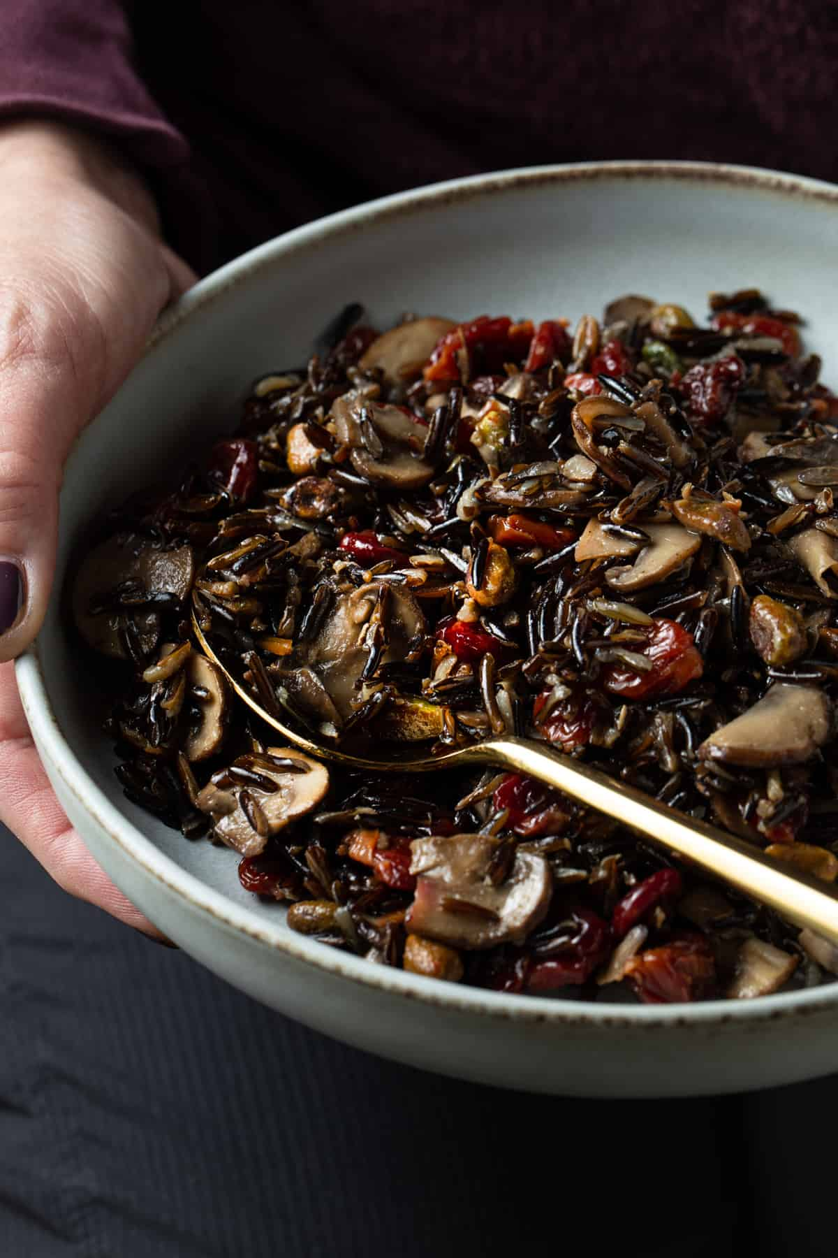 Hands holding a gray bowl filled with cooked wild rice.