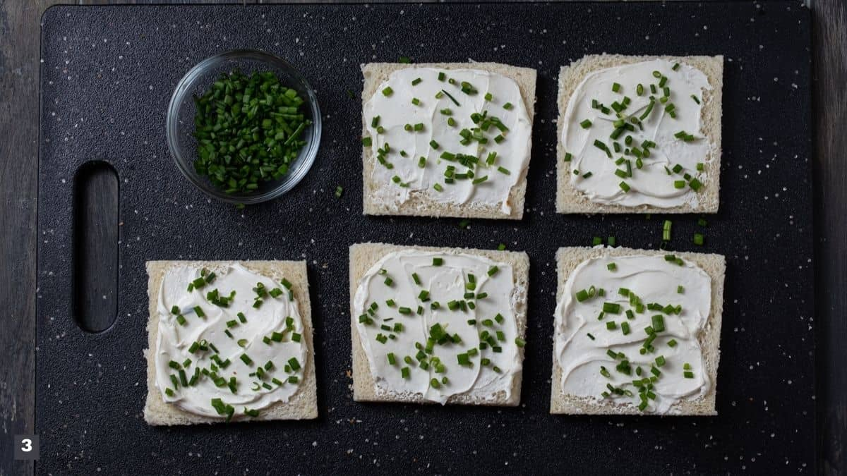 Slices of bread with cream cheese and chives on top.