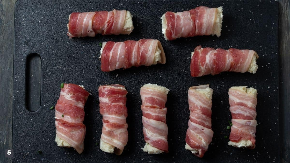 Pieces of bread rolled with bacon spiraled around.
