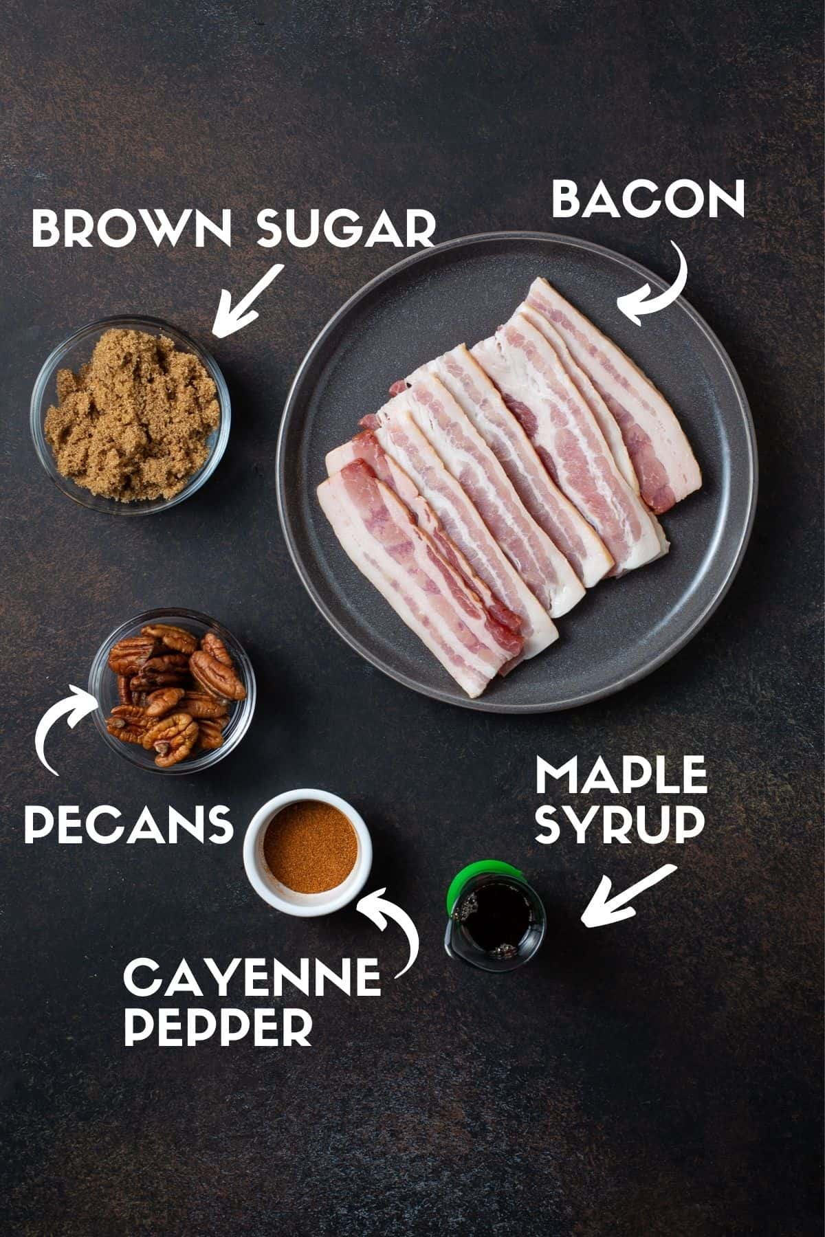 bacon, pecans, brown sugar, maple syrup and cayenne pepper on black board.