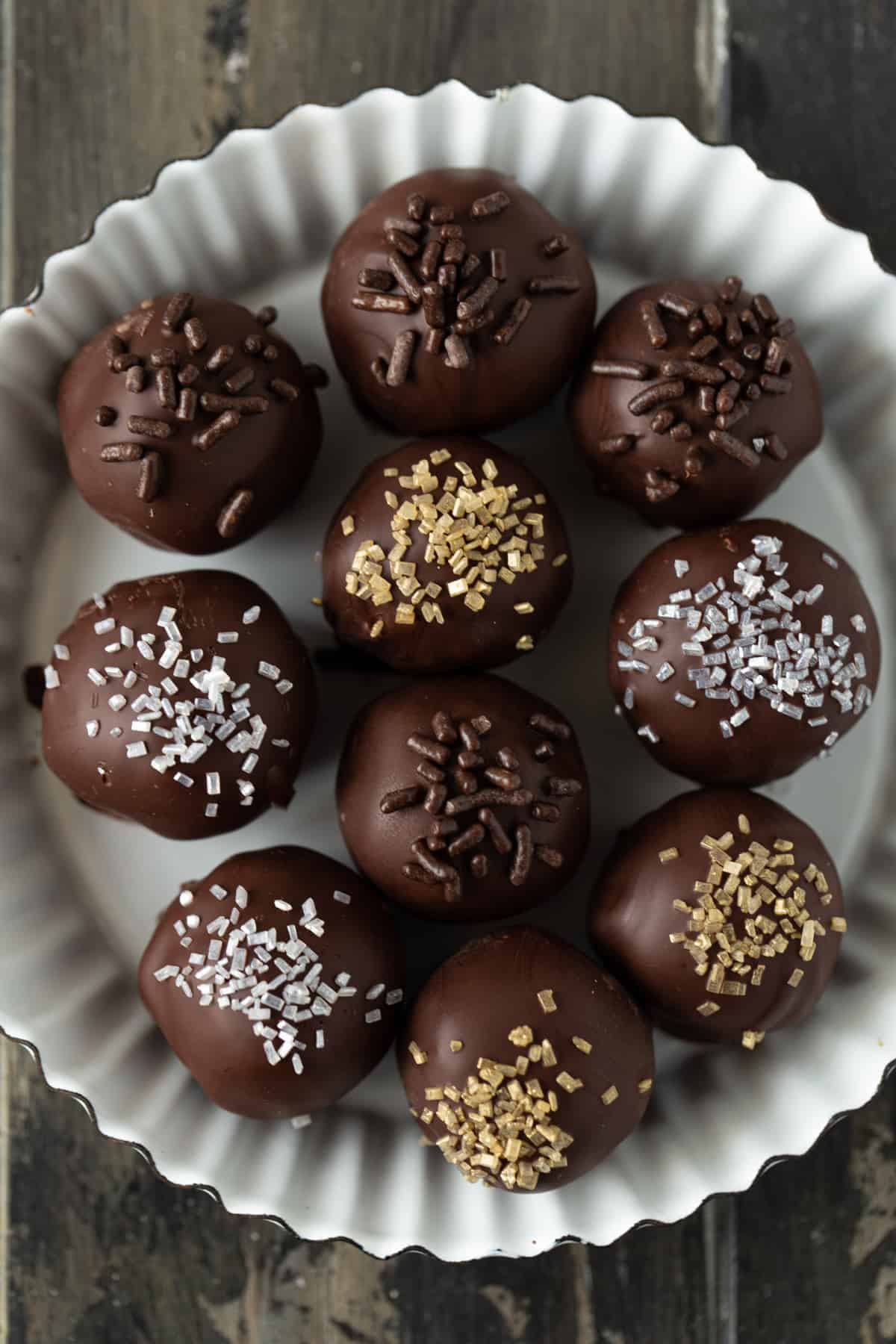 Chocolate dipped truffles in a small white metal fluted tart pan.