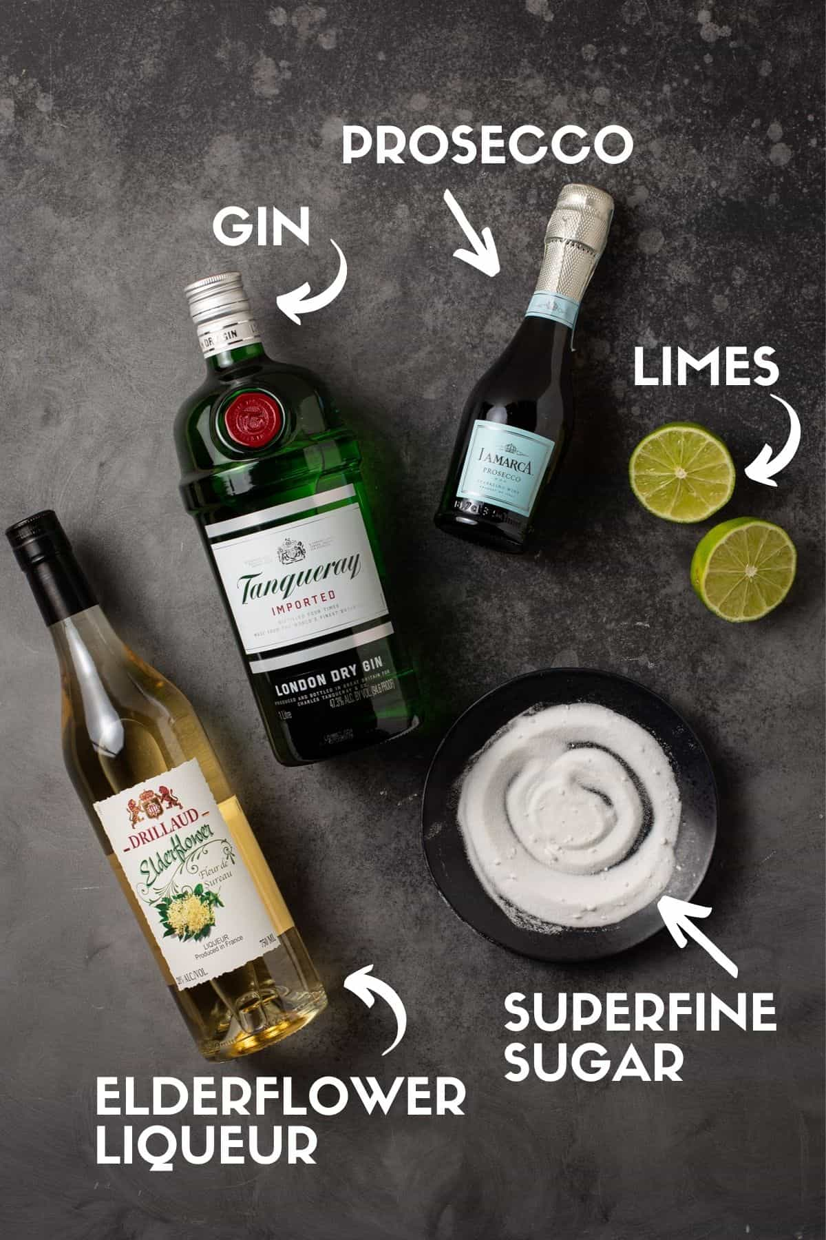 elderflower, superfine sugar, limes, prosecco and gin on a black surface.
