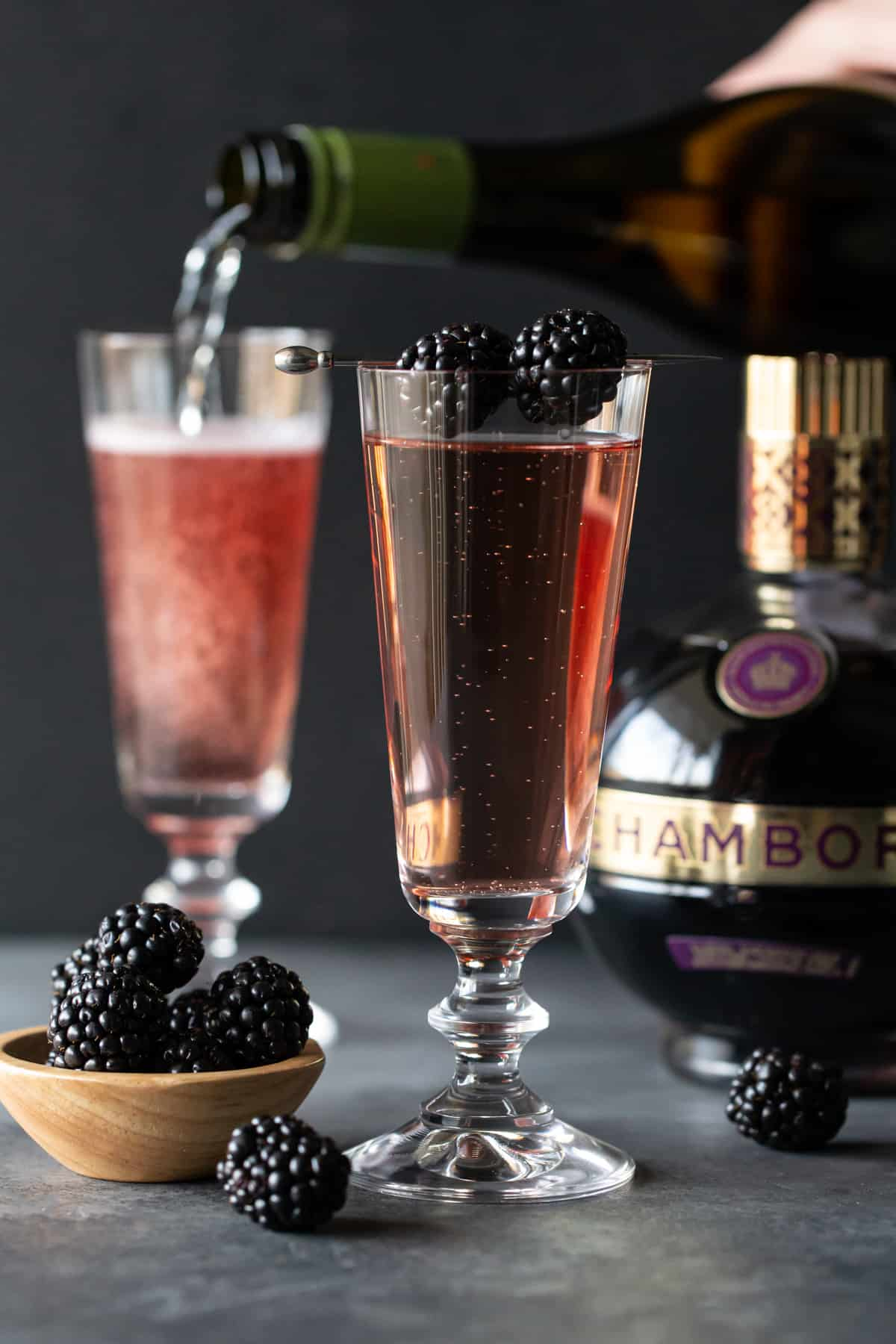 Flutes of cocktail on a dark board with blackberries.