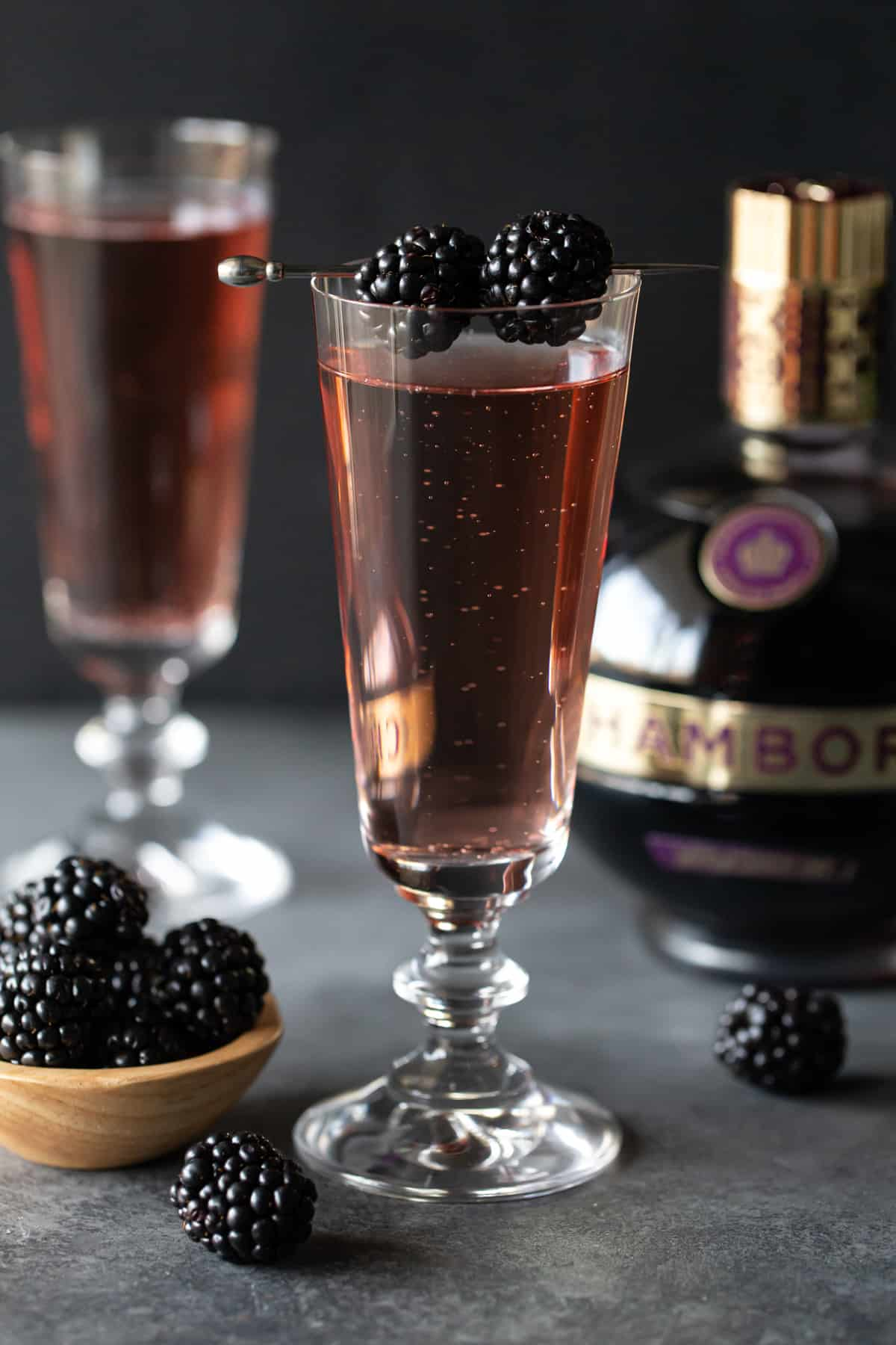 Drinks in footed glasses with blackberries.