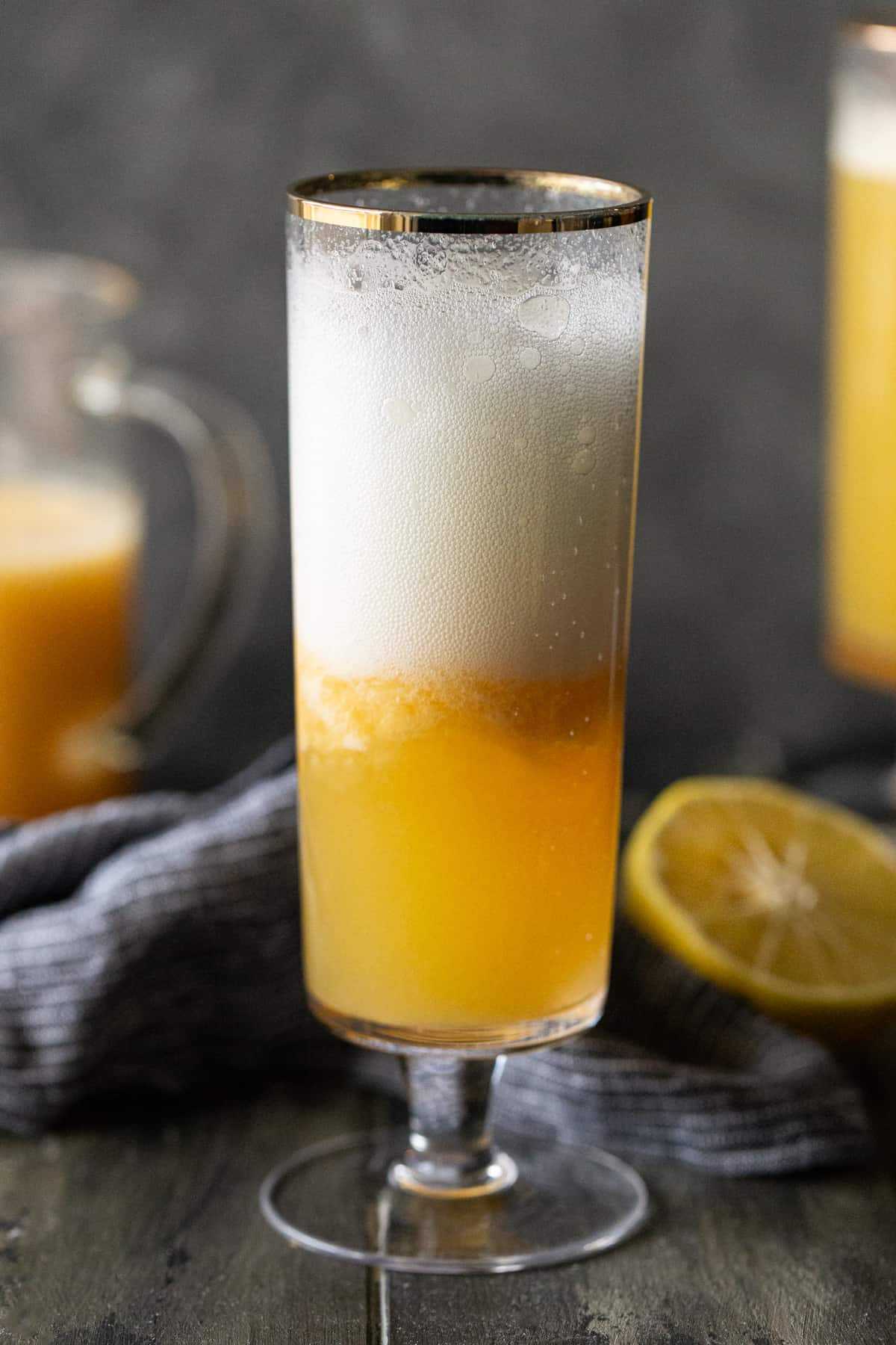 A glass of orange juice next to a pitcher, with Bellini and Non-alcoholic drink.