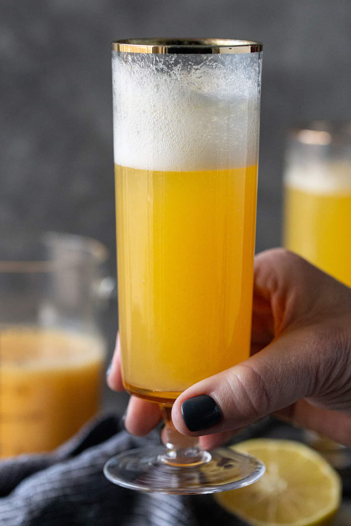 A person holding a glass of bellini on a table, with peach juice and Prosecco.