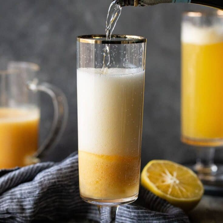 A pitcher of peach juice and a glass of peach juice, with Bellini.
