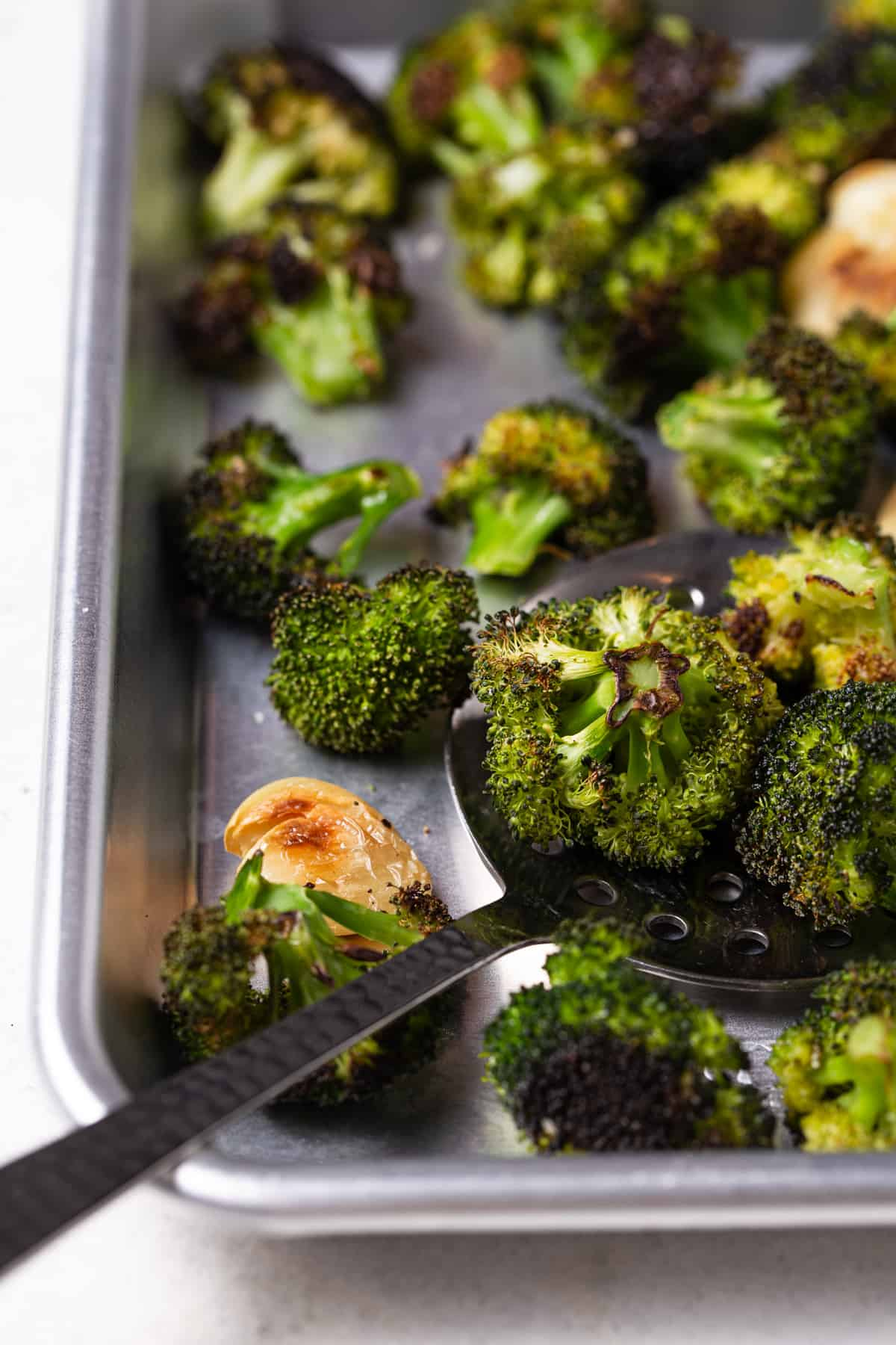 Baked broccoli on a sheet pan with serving spoon.