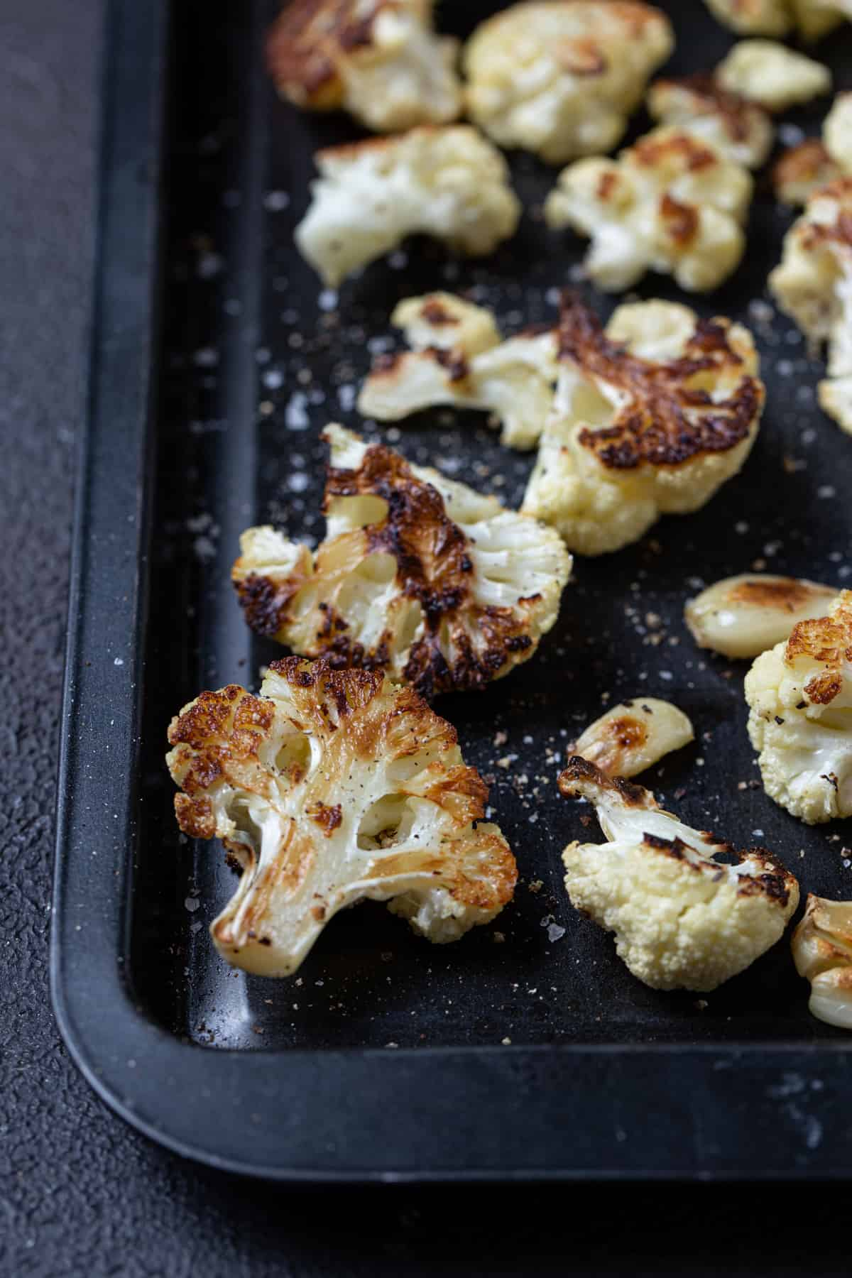 close up of cauliflower on sheet pan with salt and pepper.