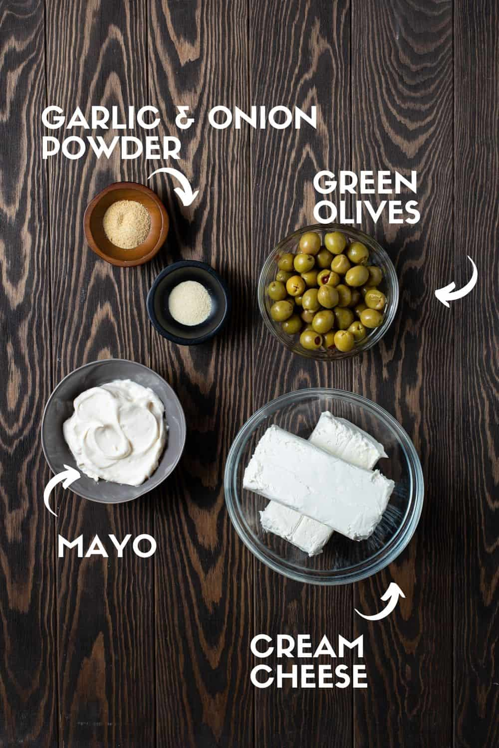 ingredients needed for olive dip on brown board.