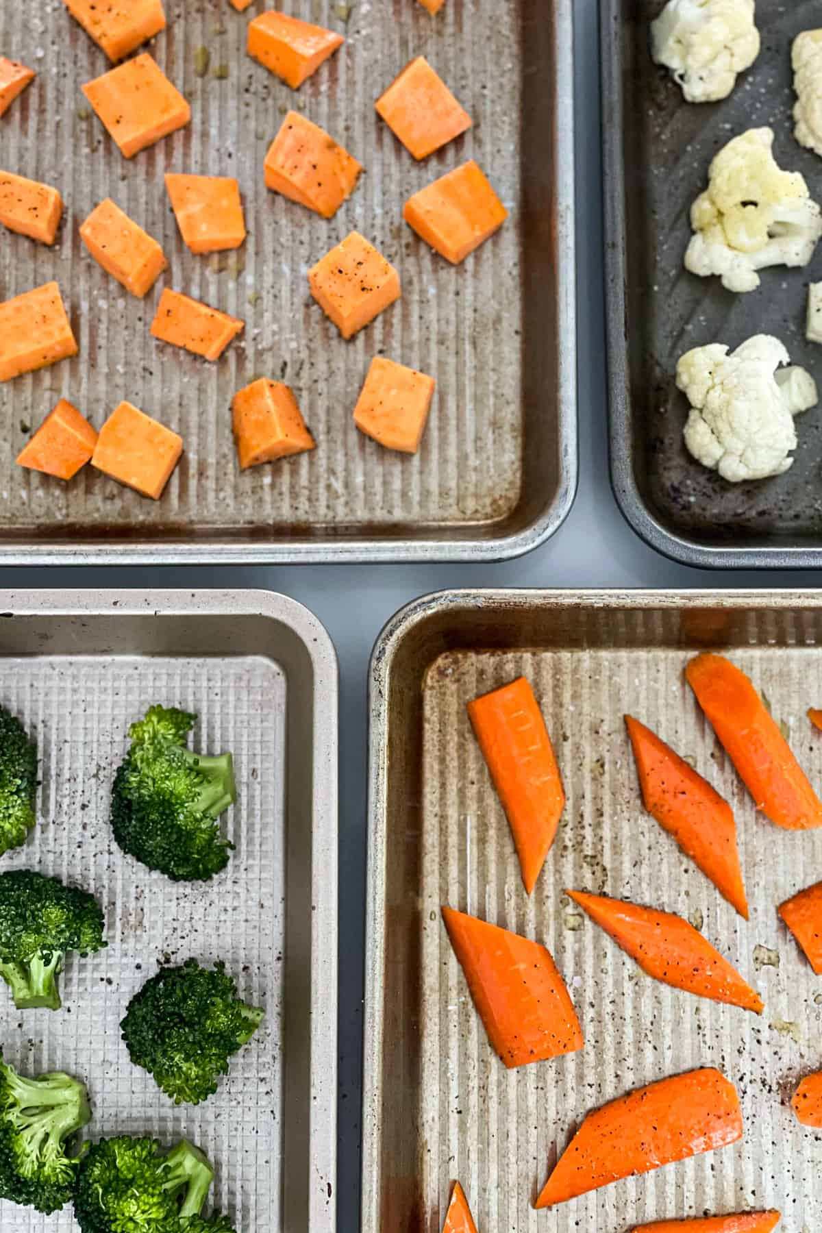 Four sheet pans with chopped vegetables.