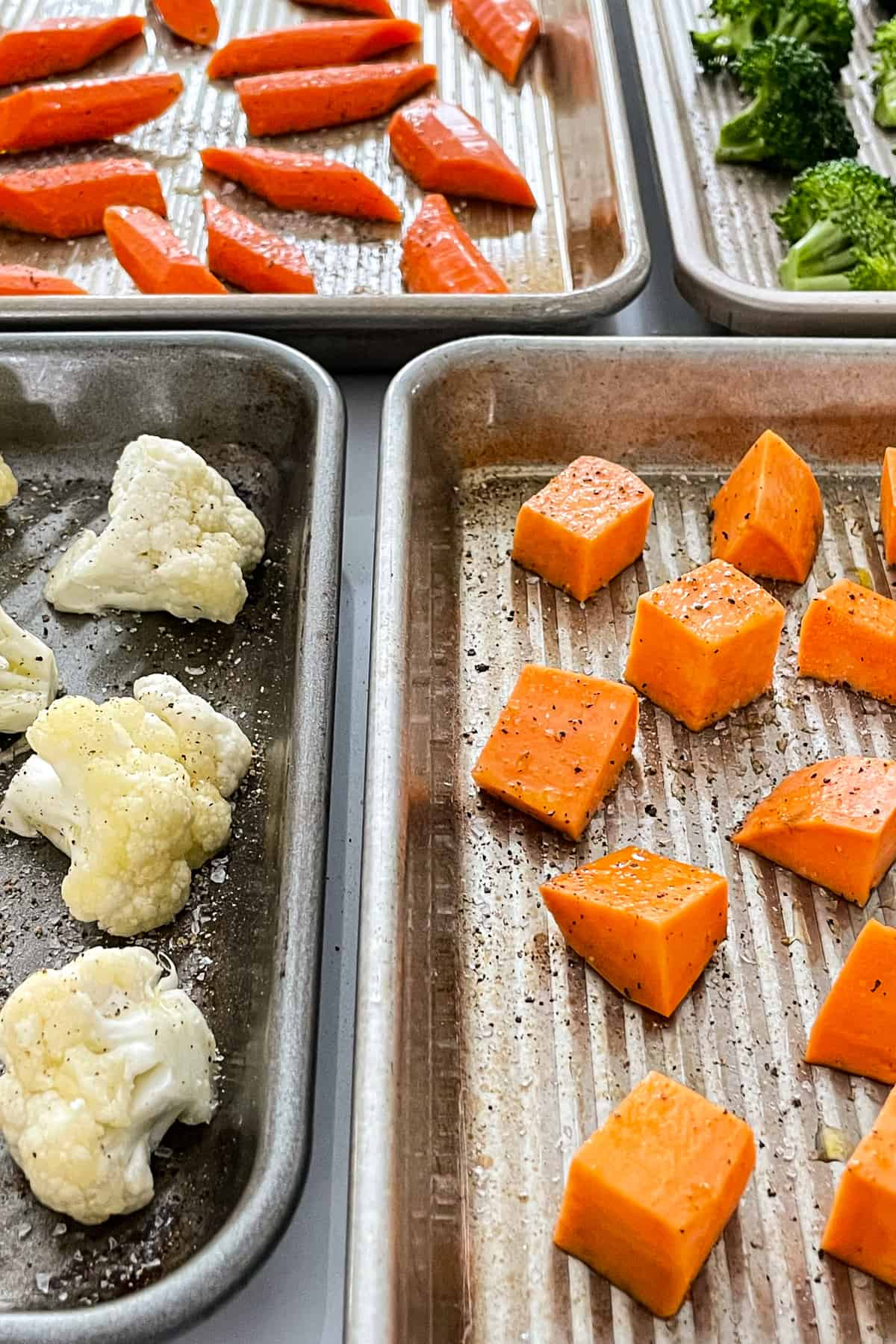 Sheet pans filled with chopped fresh vegetables.