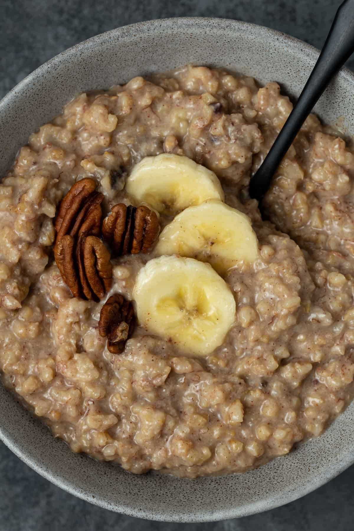 Gray bowl filled with Slow Cooker Steel Cut Oats with Bananas.
