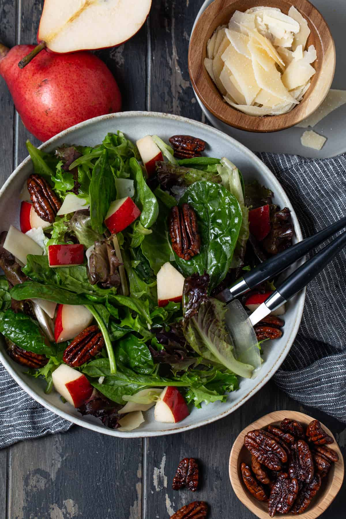 Pear salad in a gray bowl surrounded by pecans and parmesan cheese.