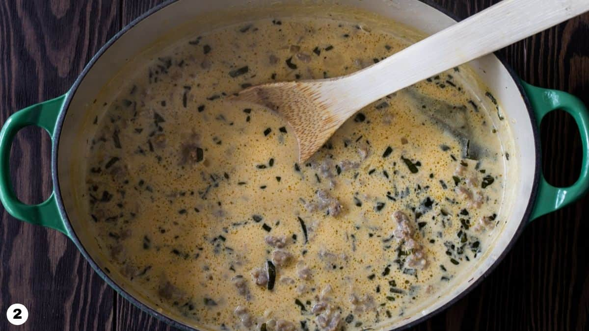 Creamy pumpkin pasta sauce with sausage in a dutch oven.