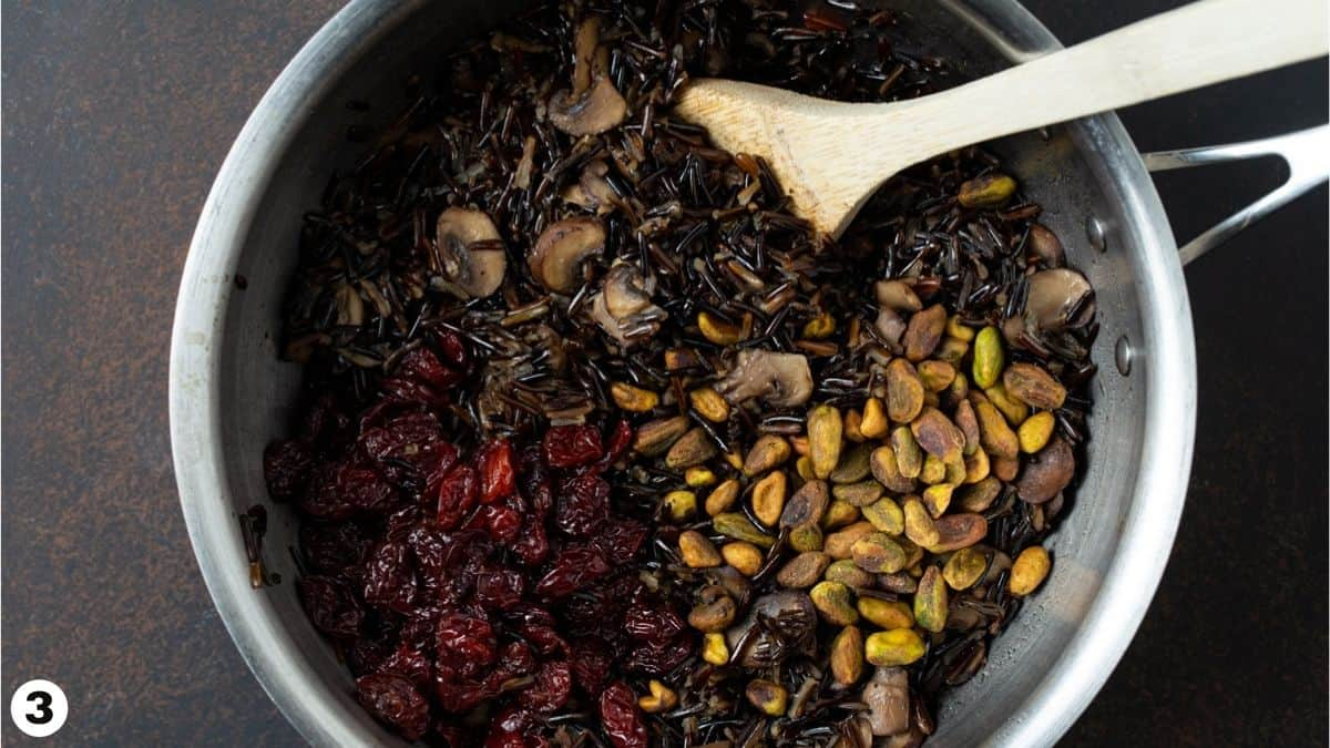 Pistachios, dried cherries, mushrooms and wild rice in pan.