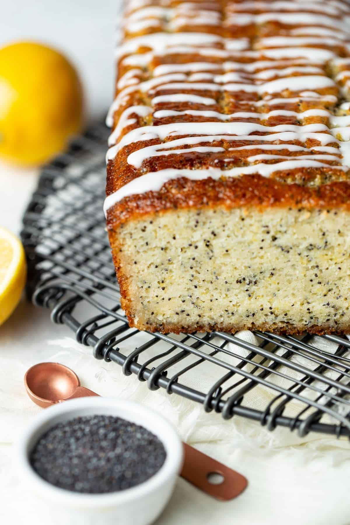 Loaf of lemon poppy seed bread drizzled with glaze on a wire cooling rack