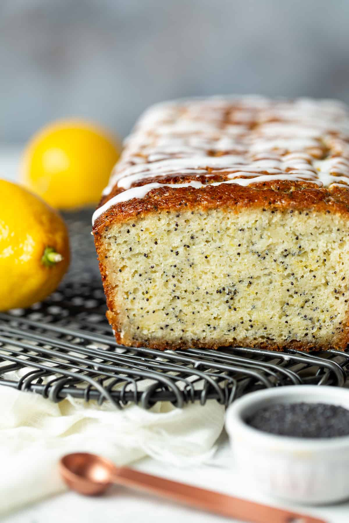 Loaf of lemon poppy seed bread drizzled with glaze on a cooling rack.