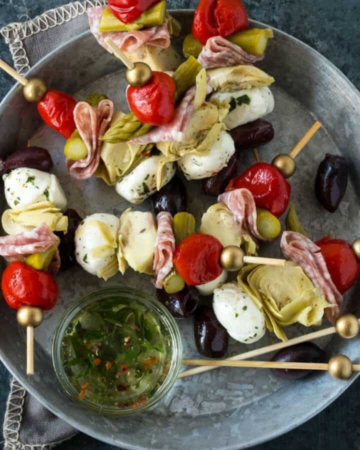 silver tray filled with appetizer skewers with dipping sauce,