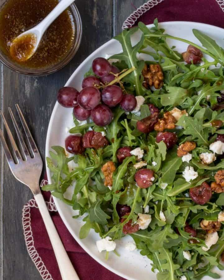 green salad on silver plate with roasted grapes.