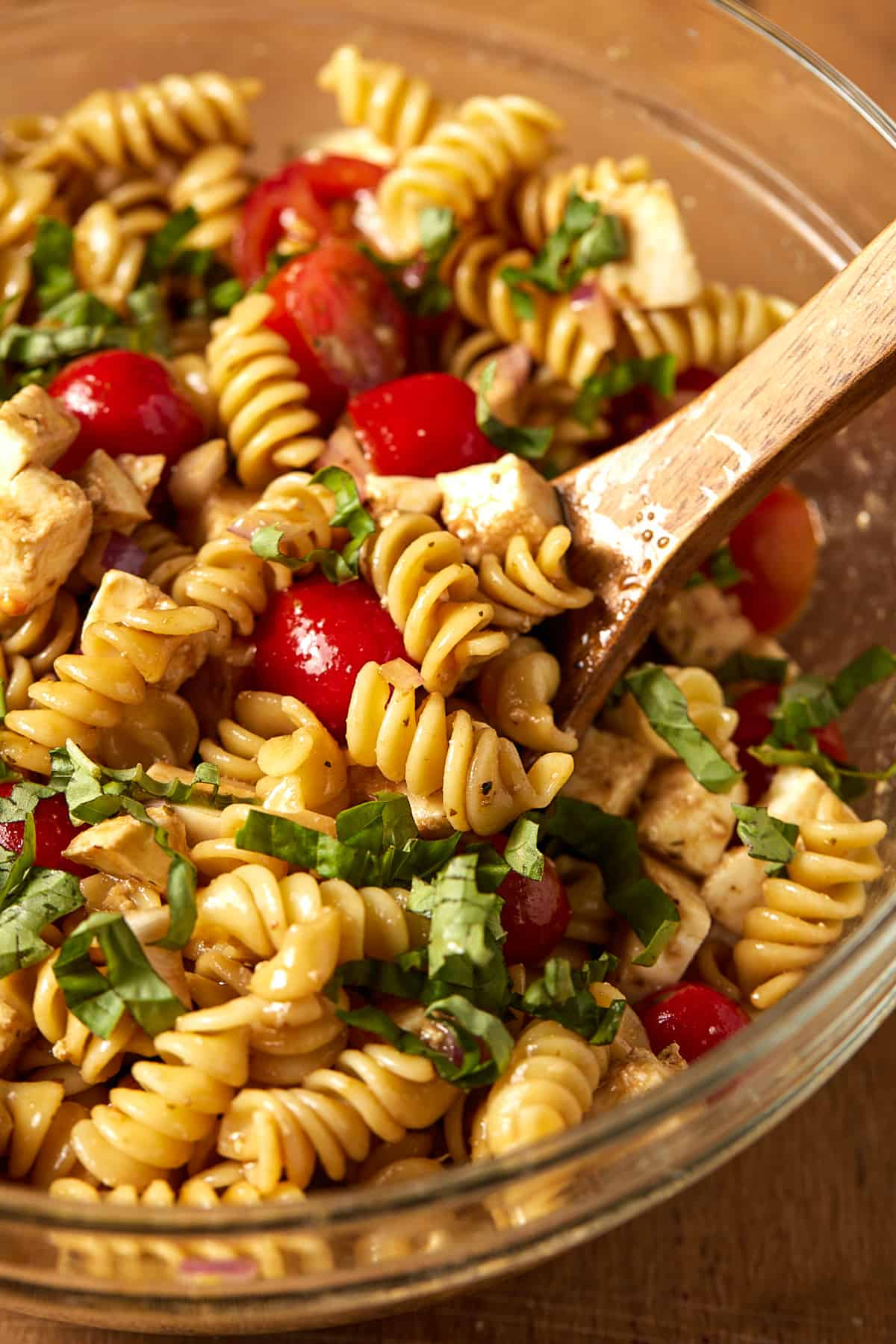 glass bowl with pasta, basil tomatoes and spoon.