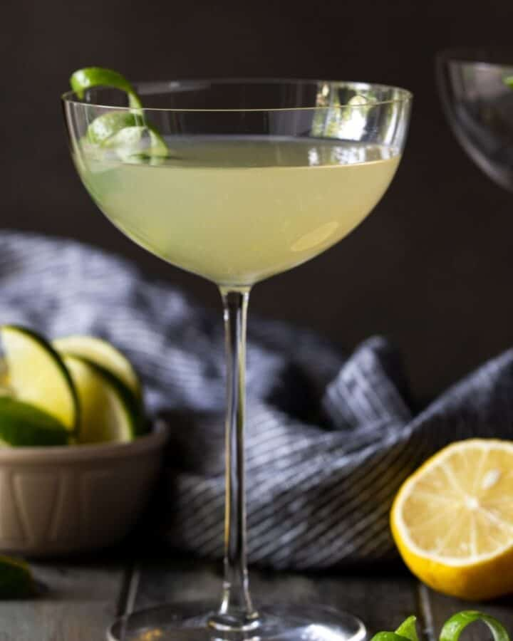 tall martini glass filled with drink on table with lemon wedges.
