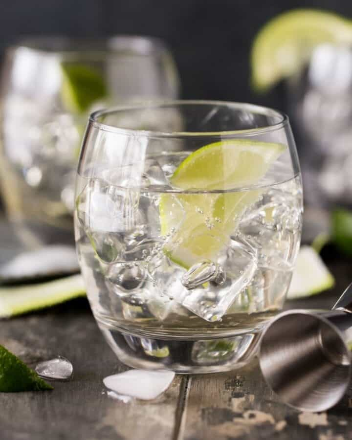 low ball glass filled with ice and cocktail with lime wedge.