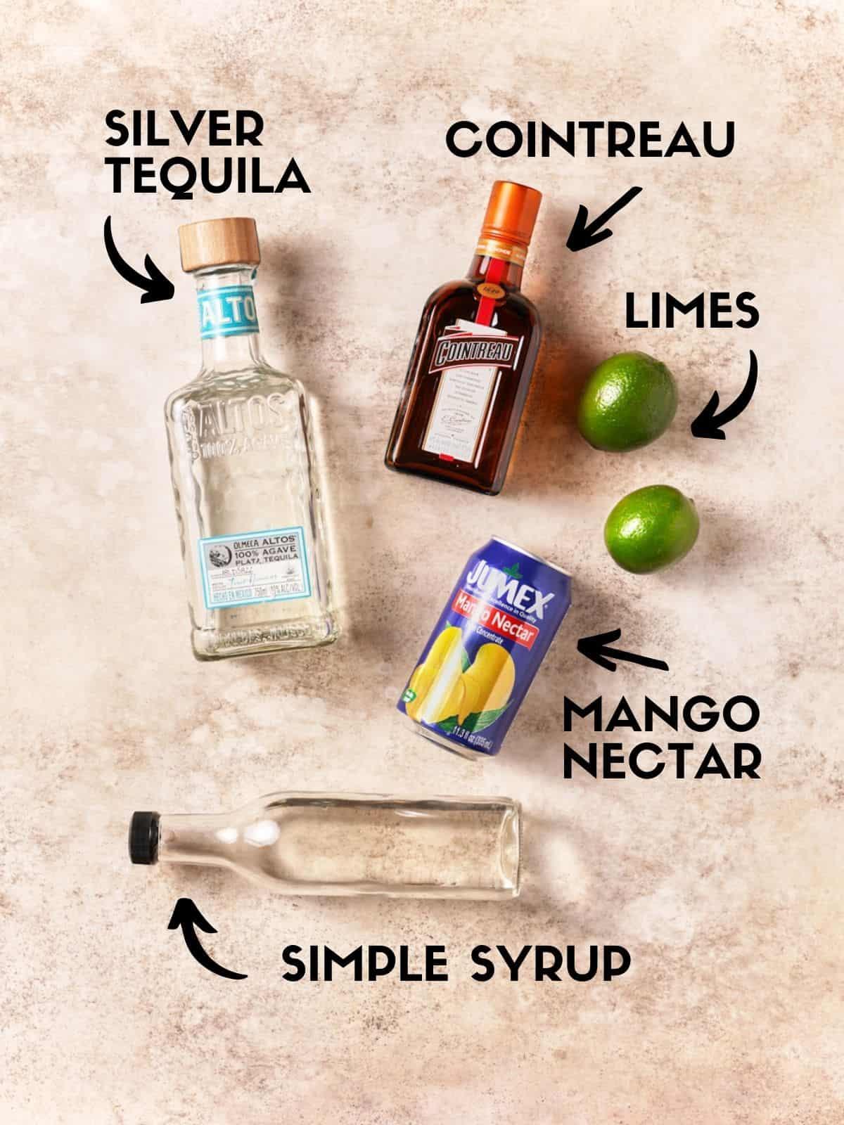 Ingredients to make mango margaritas, including tequila, orange liqueur and mango nectar.