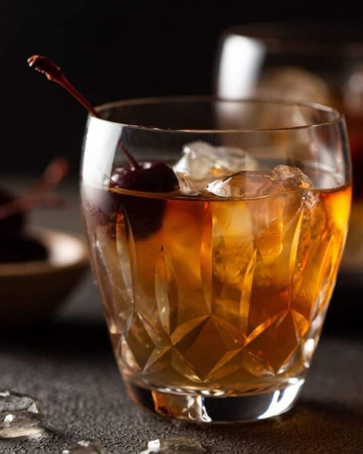 single low ball glass filled with drink and cherry for garnish.