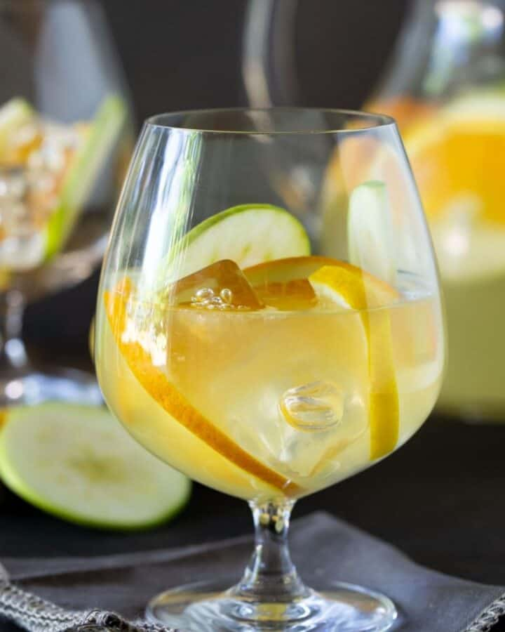 balloon glass filled with sangria and apples, lemon and oranges.