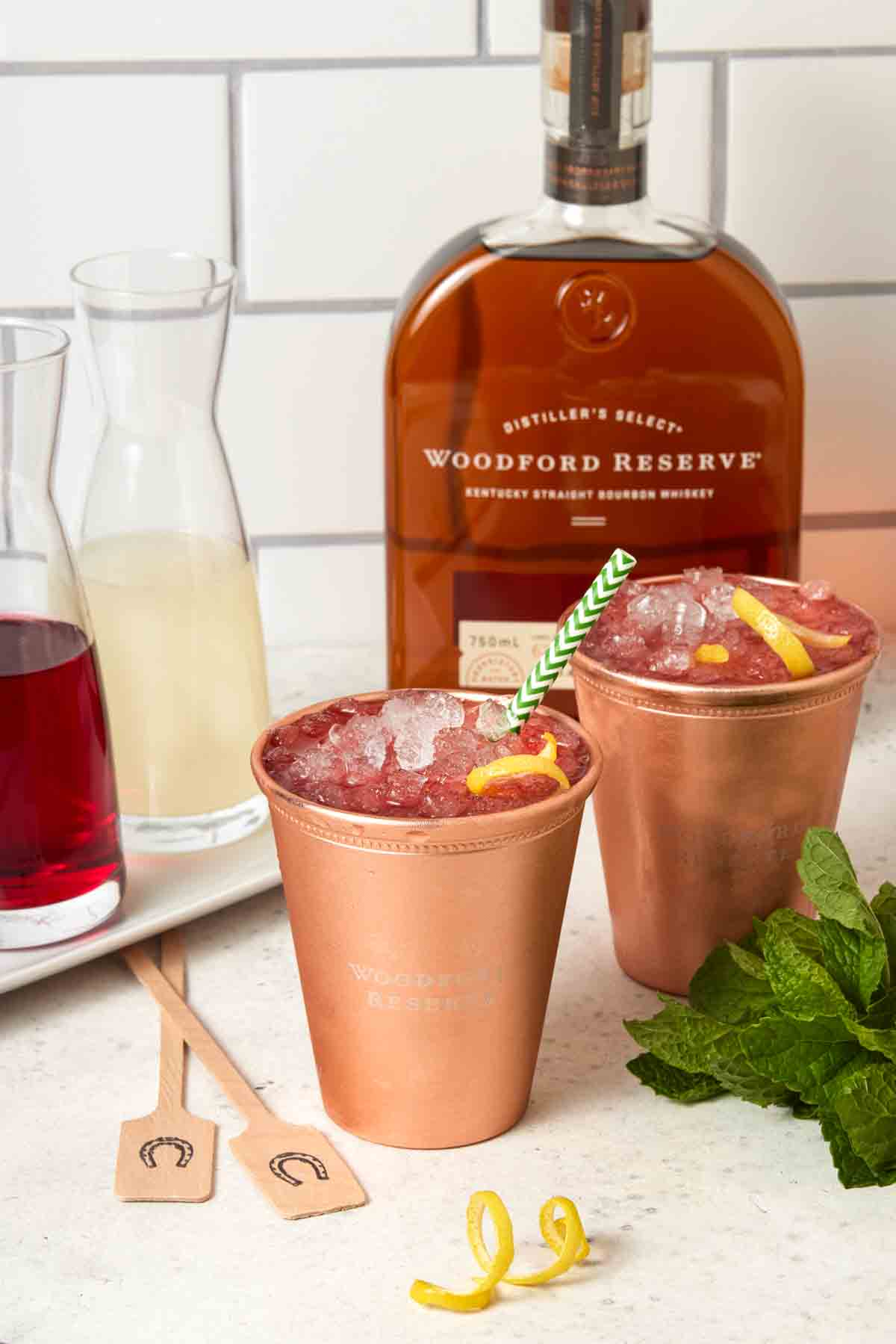 Two glasses of Woodford Spire Cocktails in ice-filled copper cups.