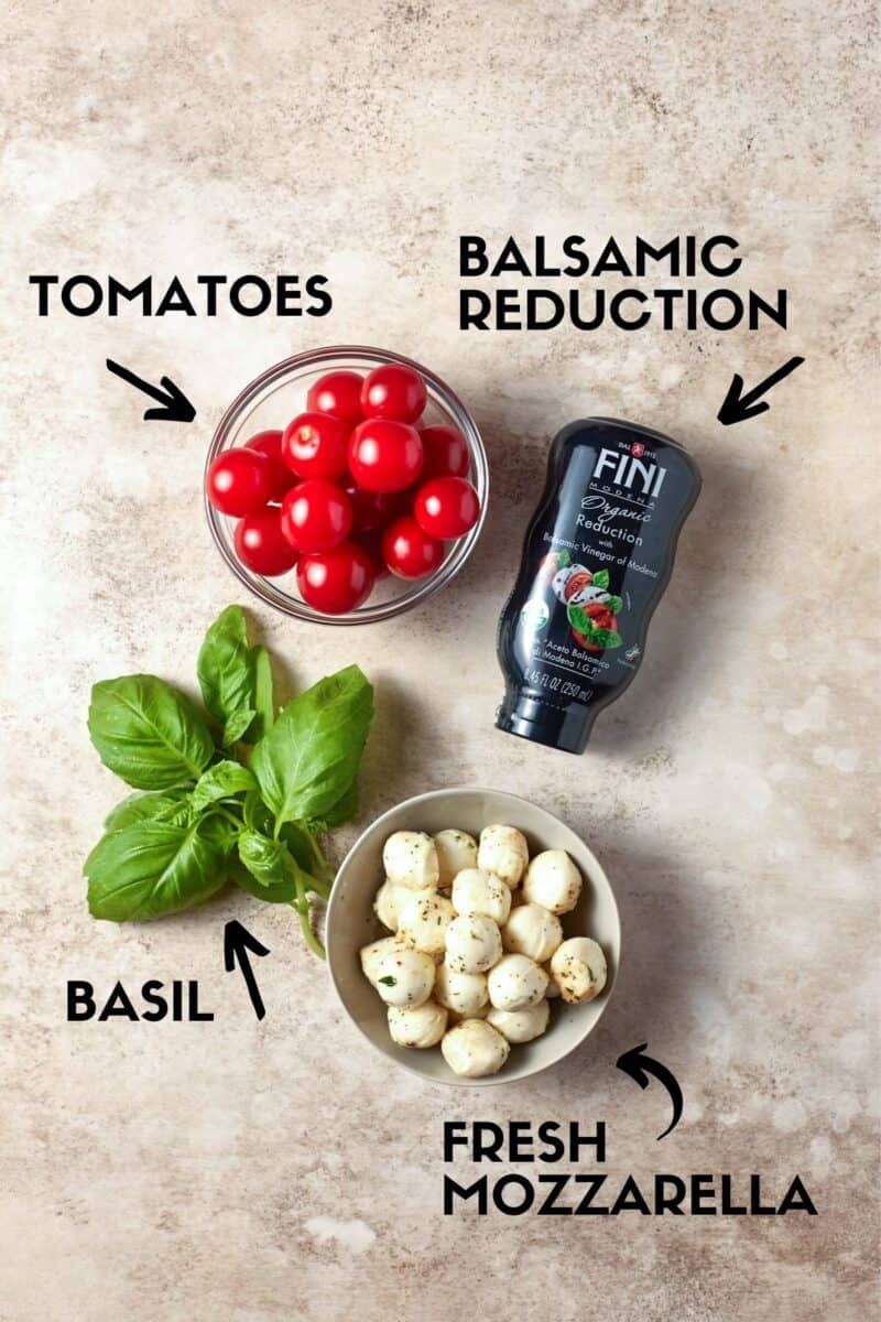 Ingredients for Caprese Skewers including cherry tomatoes, fresh mozzella balls, basil and balsamic glaze.