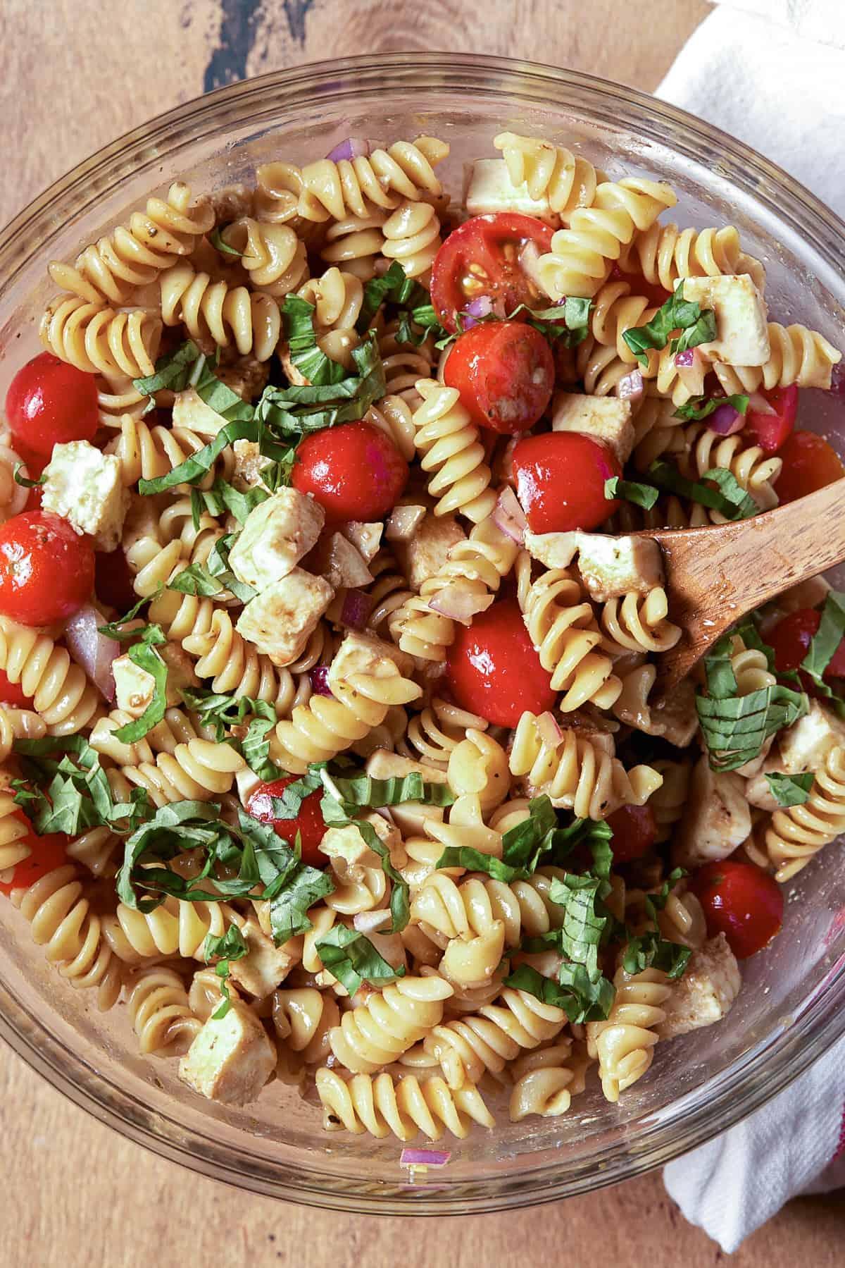 Caprese pasta salad in a glass bowl.