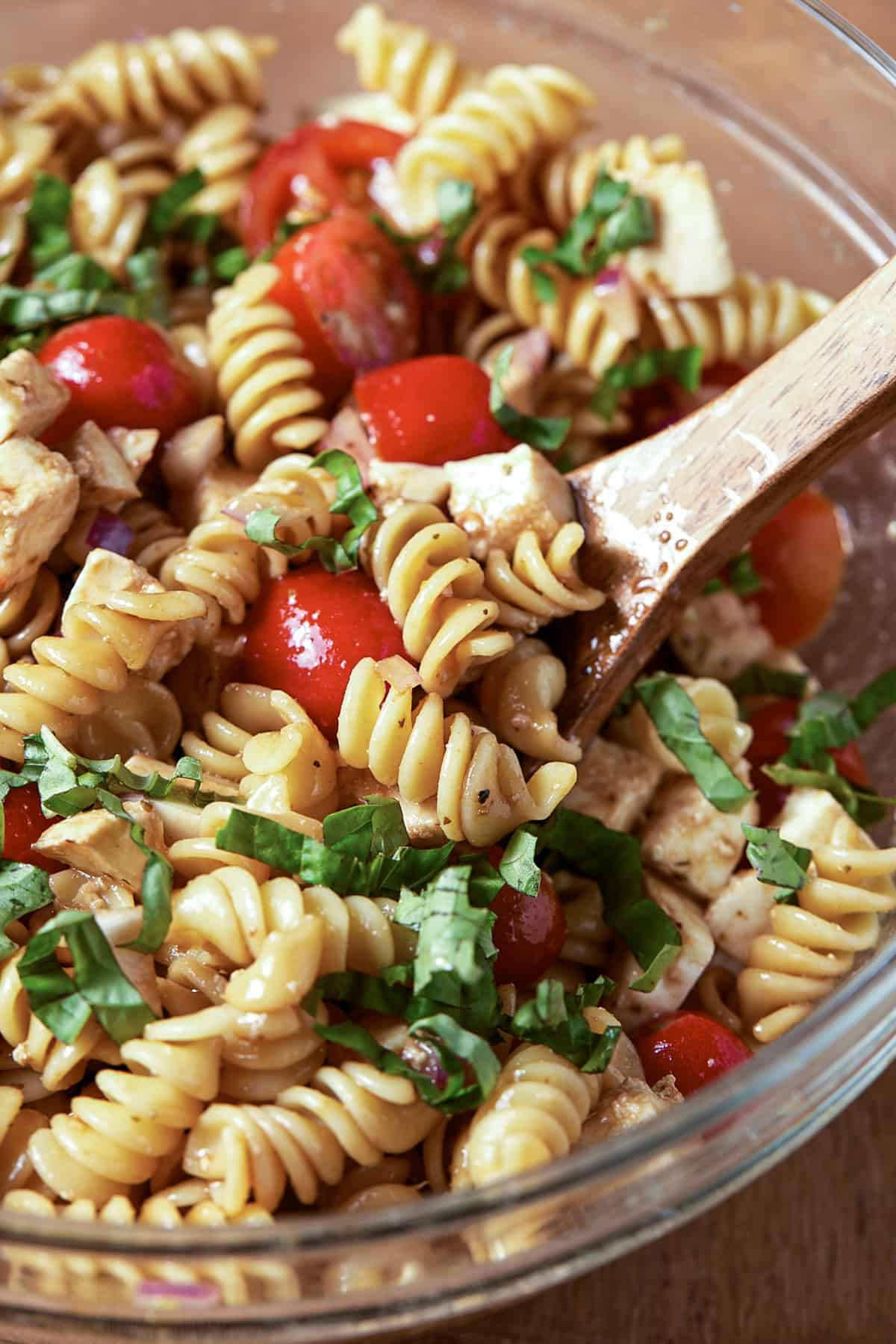 Glass bowl with pasta, basil, tomatoes and spoon.