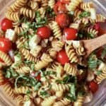 Caprese pasta salad in a glass bowl with a wooden spoon on the side.