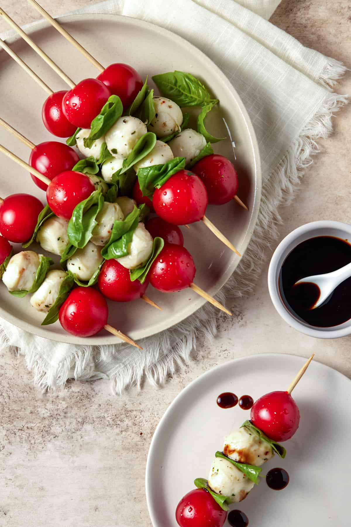 Two plates filled with caprese skewers and drizzled with balsamic glaze.