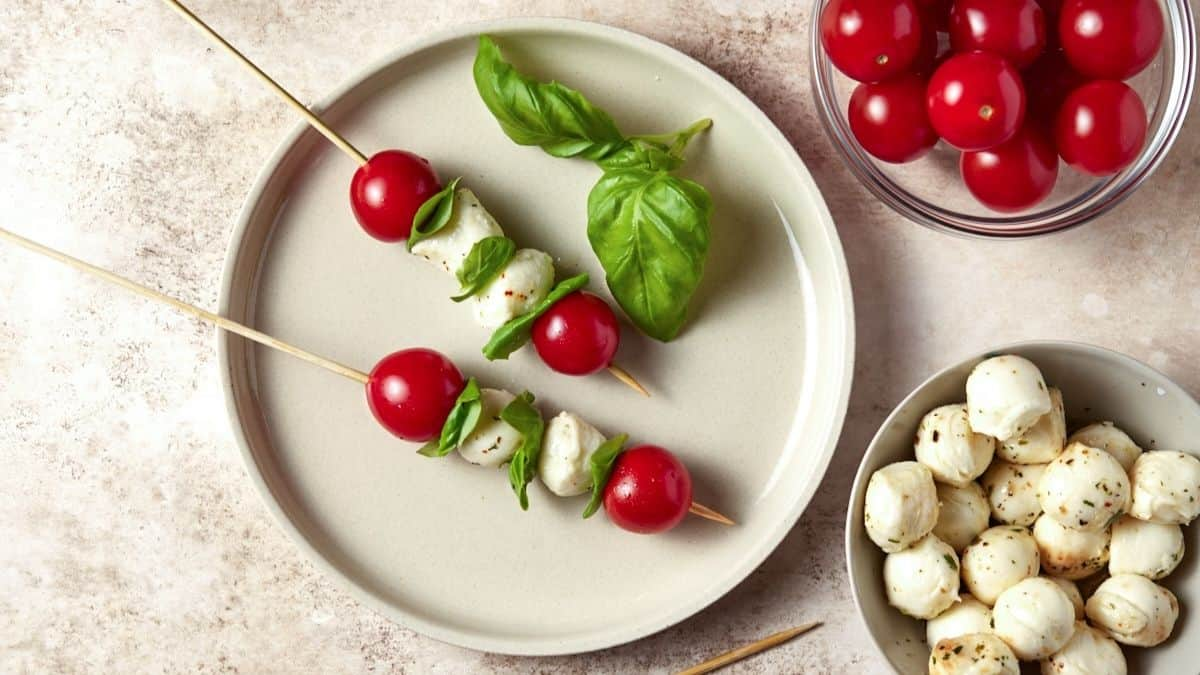 Two Caprese Skewers on a light plate with bowls of tomatoes and mozzarella balls nearby.