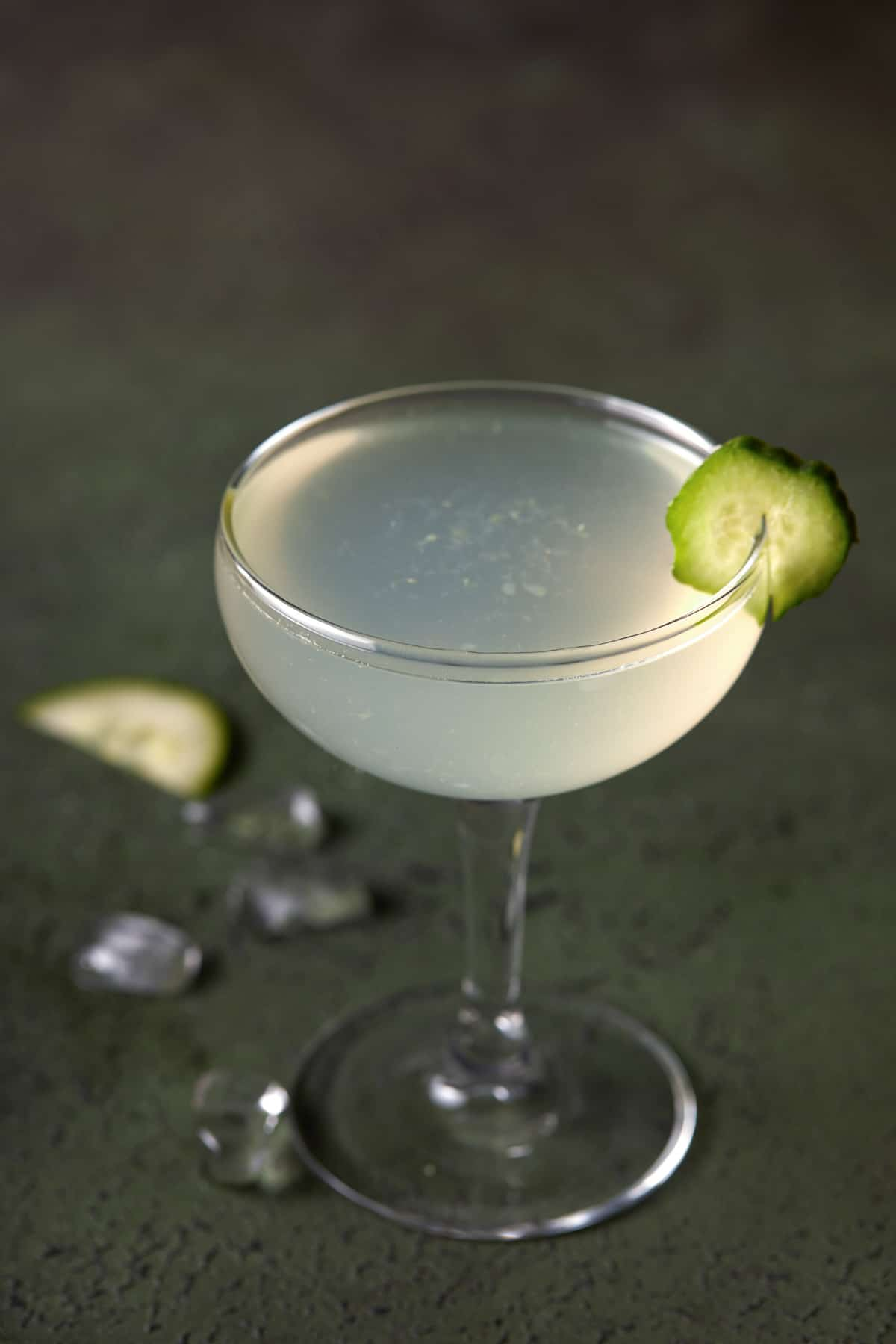 Vodka gimlet in a coupe glass garnished with cucumber on a dark green board.