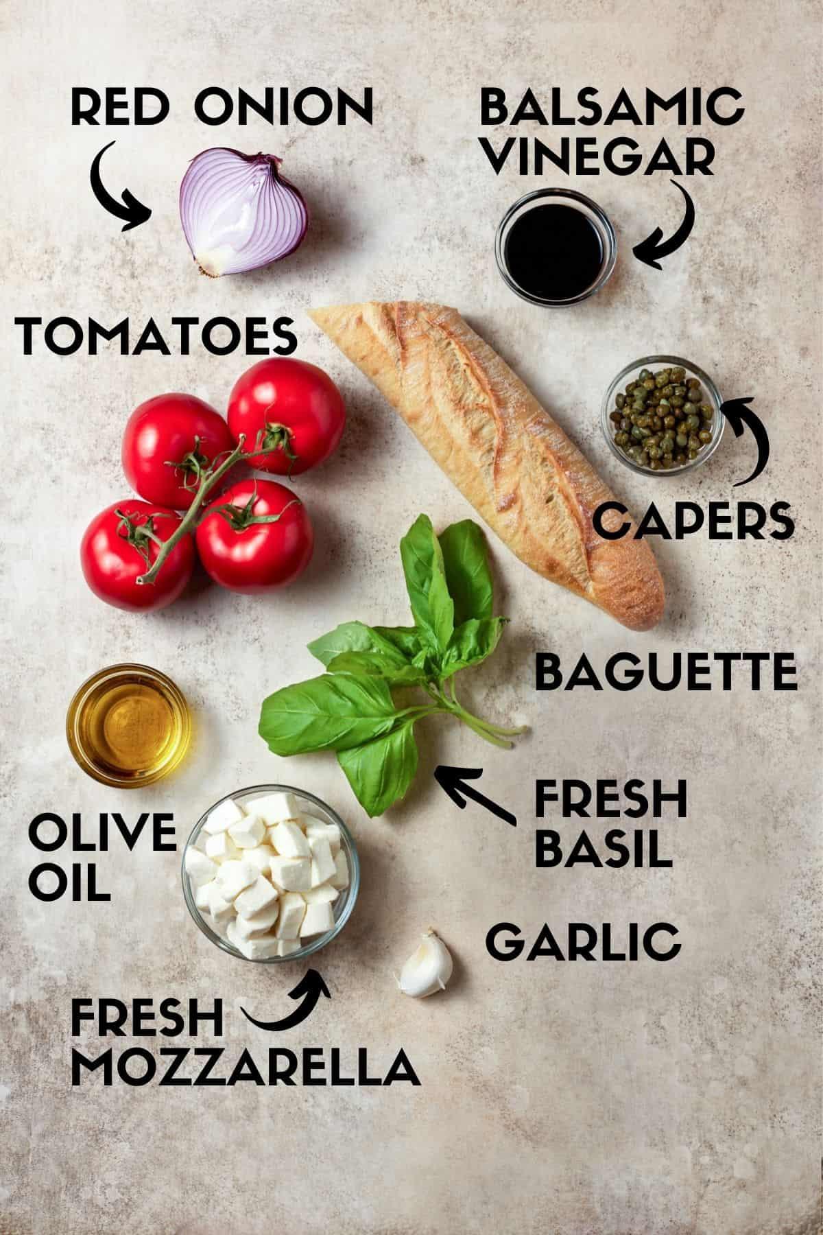 Panzanella salad ingredients including tomatoes, mozzarella cheese, bread and fresh basil.