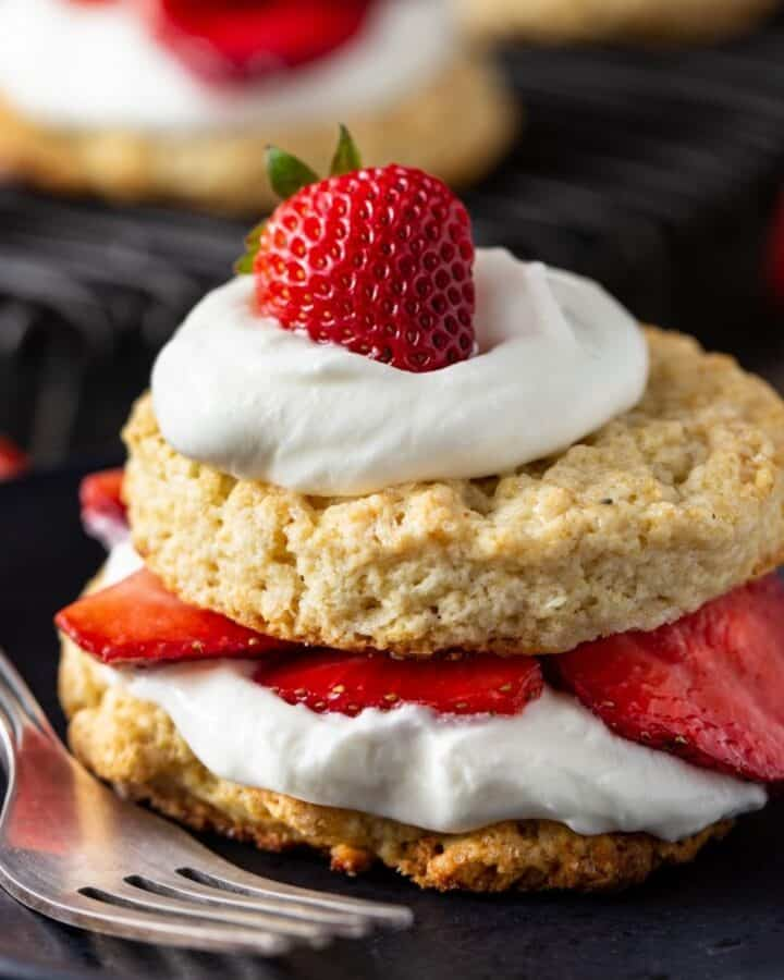 Strawberry shortcake biscuit on a black plate with a fork on the side.