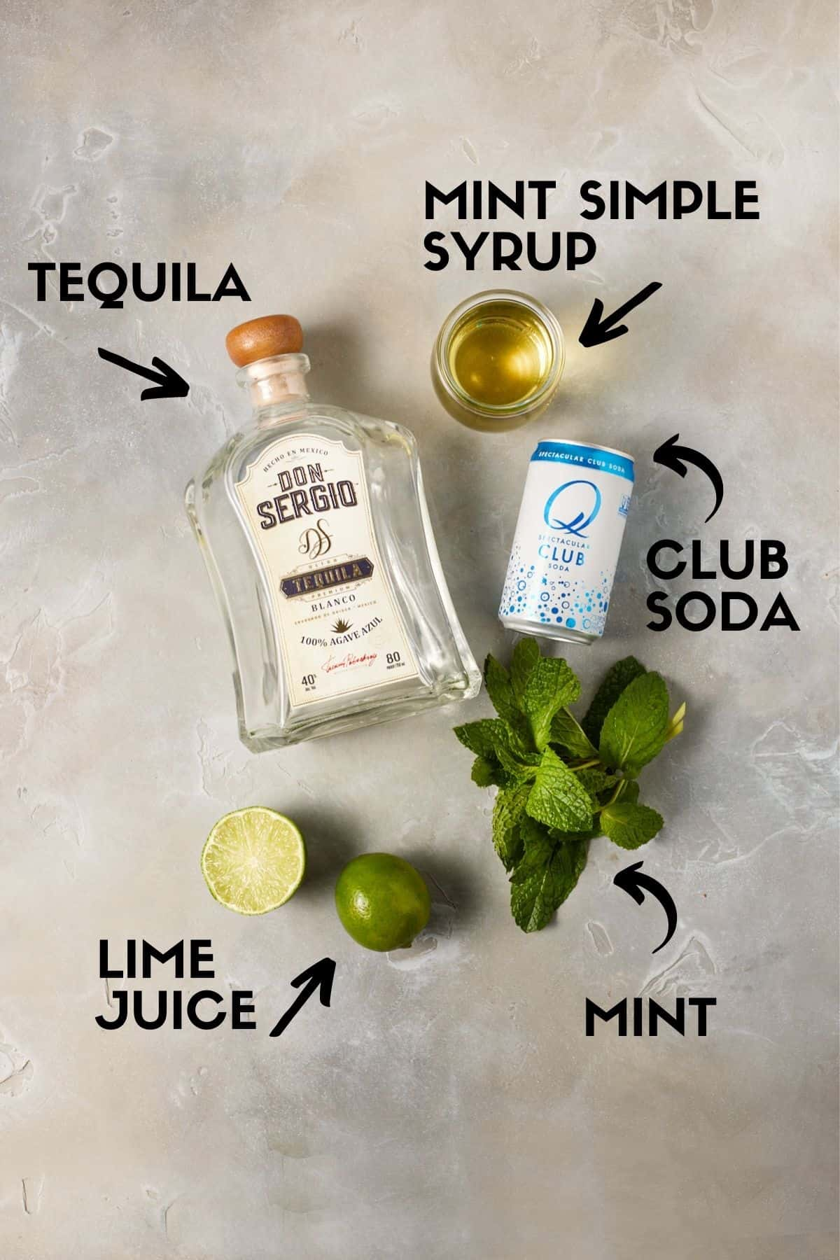 Ingredients for cocktail including tequila, club soda, lime juice and mint.