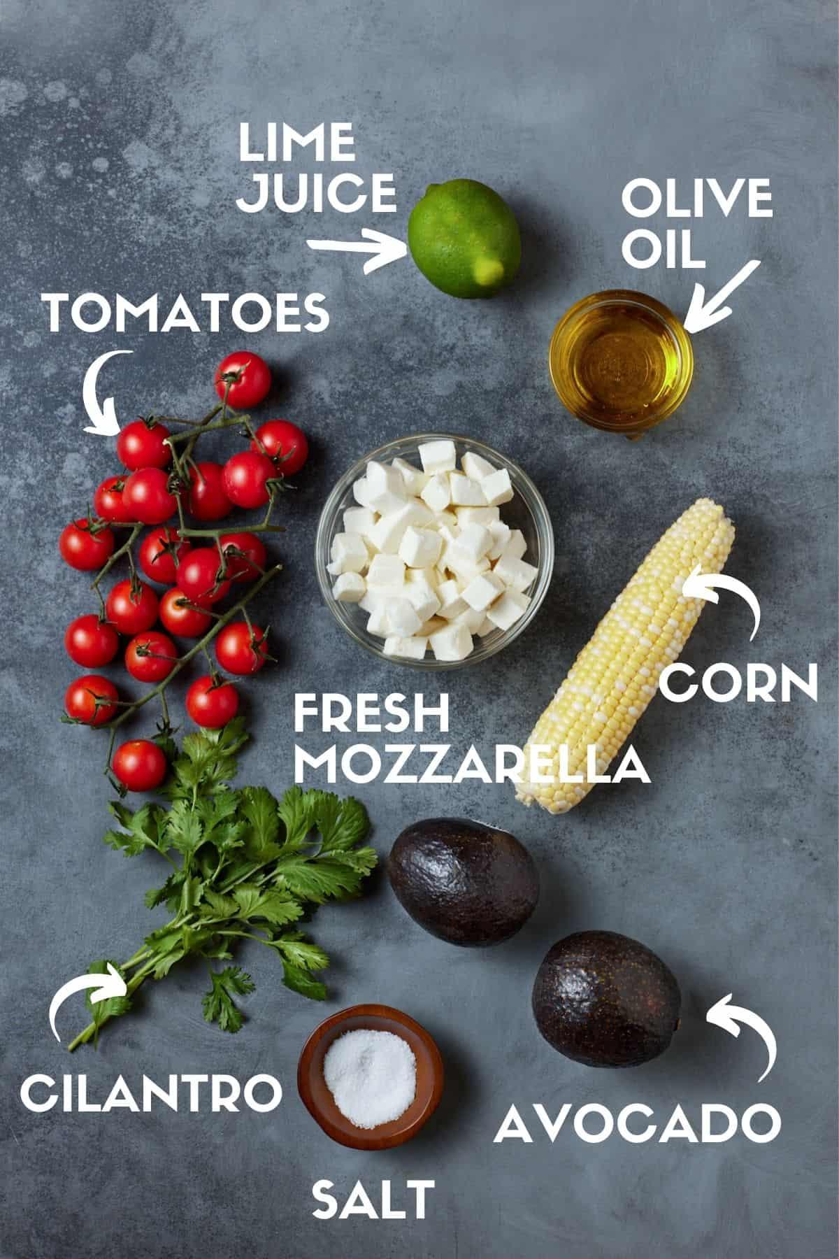 Ingredients for Corn Avocado Salad, including tomatoes, fresh mozzarella and cilantro.