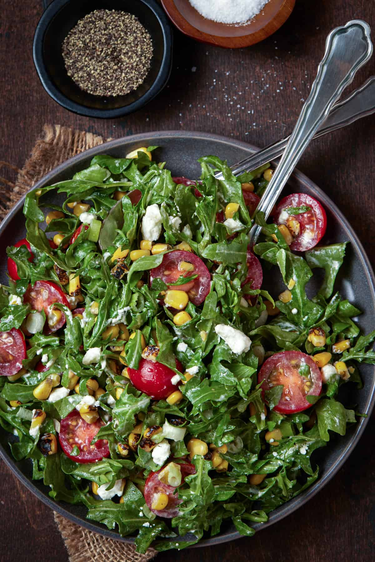 Gray bowl filled with arugula , corn and tomatoes with goat cheese and a fork.