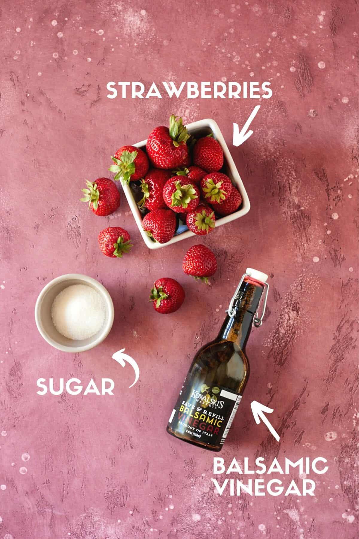 Strawberries, sugar and balsamic vinegar on a pink board.