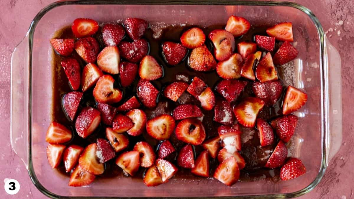 Balsamic vinegar drizzled over chopped strawberries in glass baking dish.