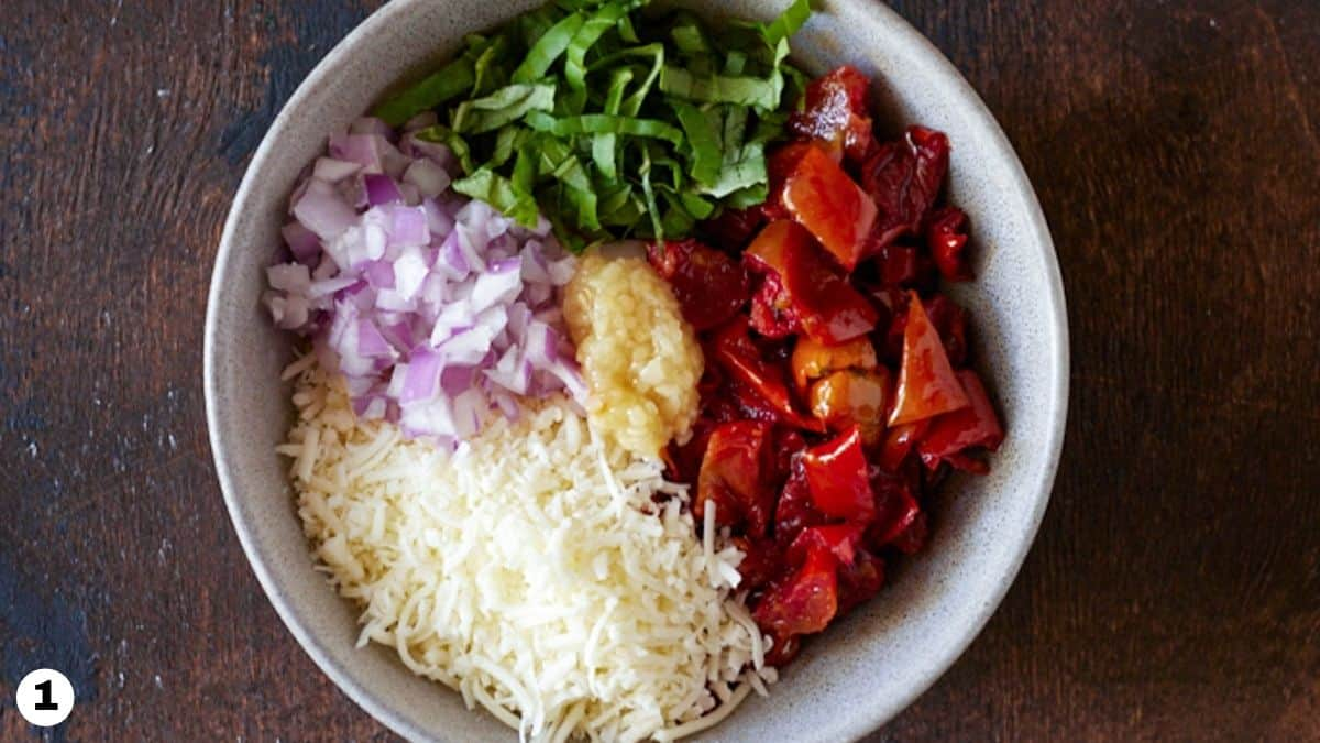 Tomato bruschetta ingredients in a grey bowl.